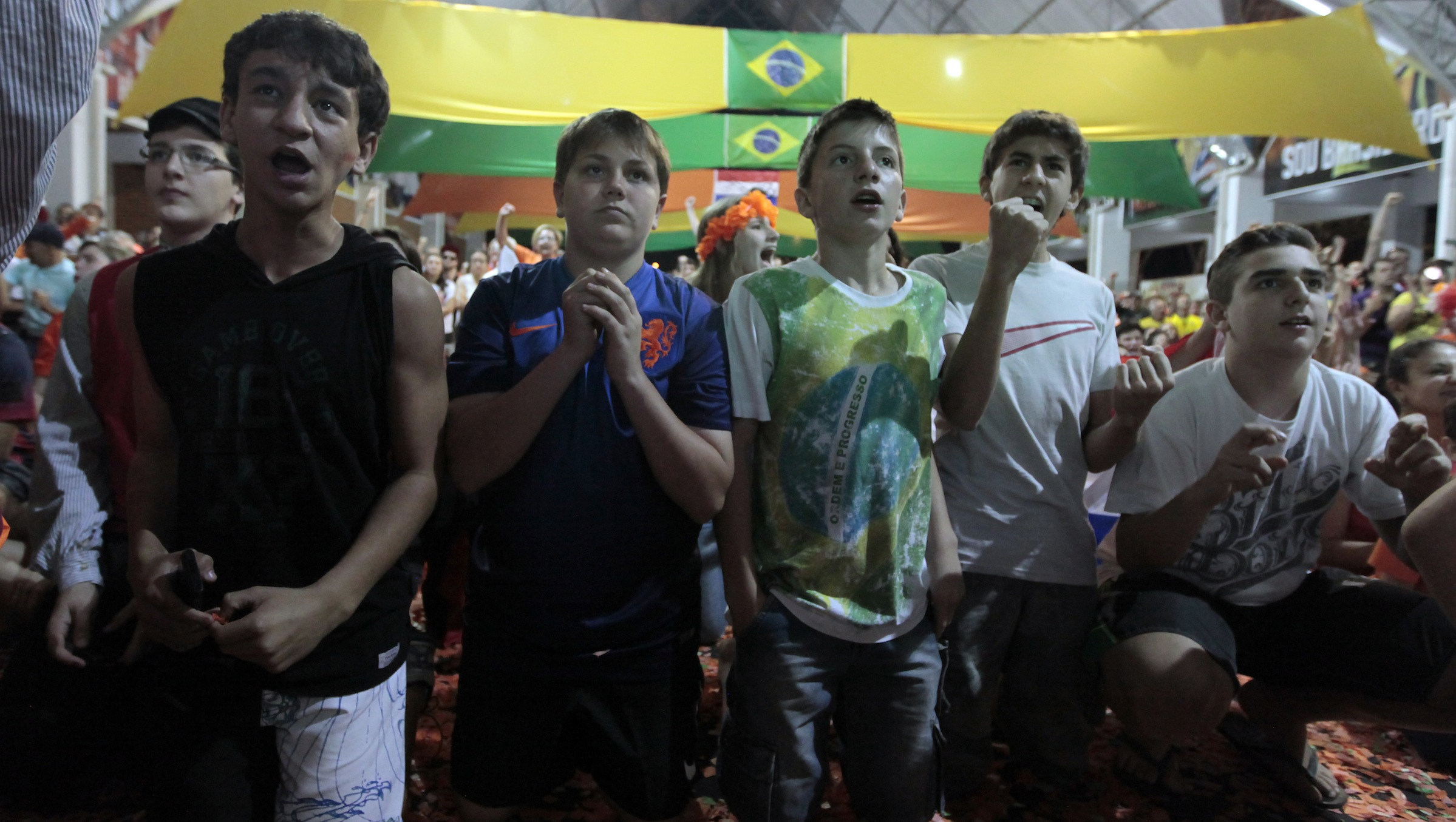 Fans kneel during the penalty shootout while watching a broadcast of the 2014 Brazil World Cup quarterfinal game between Costa Rica and the Netherlands in Holambra, a Dutch immigrant colony 140 kms north of Sao Paulo, July 5, 2014.  REUTERS/Paulo Whitaker (BRAZIL  - Tags: SPORT SOCCER WORLD CUP)   - RTR3XAJR