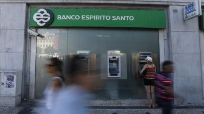 People pass near an office of Portuguese bank Banco Espirito Santo in Lisbon.