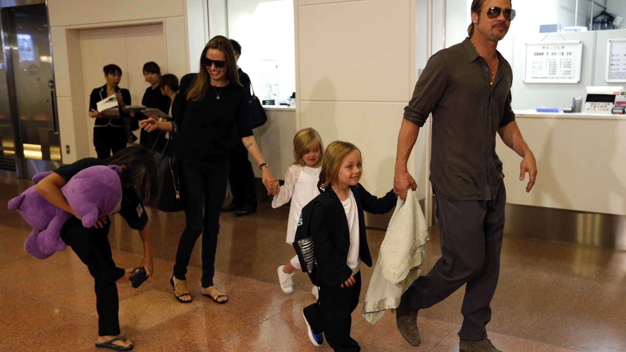 """Hollywood actor Brad Pitt (R) and actress Angelina Jolie (2nd L) arrive with their children Knox (2nd R), Vivienne (3rd R) and Pax (L) at Haneda international airport in Tokyo July 28, 2013. Pitt flew into Japan on Sunday with Jolie and their children to attend promotional events of his movie """"World War Z"""". REUTERS/Issei Kato (JAPAN - Tags: ENTERTAINMENT)"""