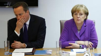 Britain's Prime Minister David Cameron and Germany's Chancellor Angela Merkel attend a meeting at a summit in Brussels.