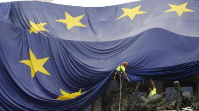 Workers hang a giant European Union flag.