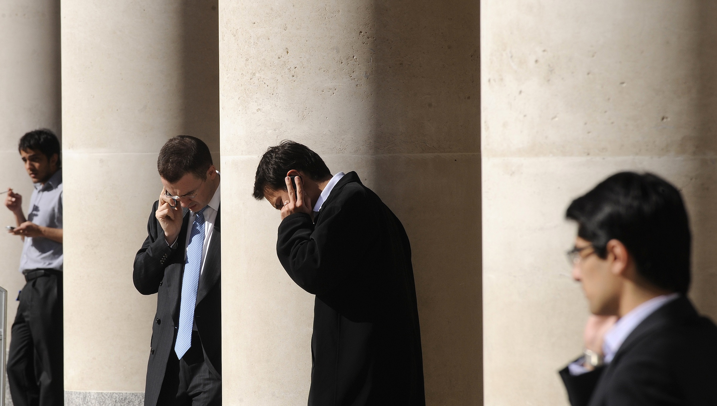City workers make phone calls outside the London Stock Exchange in Paternoster Square in the City of London at lunchtime October 1, 2008. European policymakers have called on the U.S. Senate to approve a revised rescue plan aimed at tackling the worst financial crisis since the 1930s. REUTERS/Toby Melville (BRITAIN) - RTX93SY