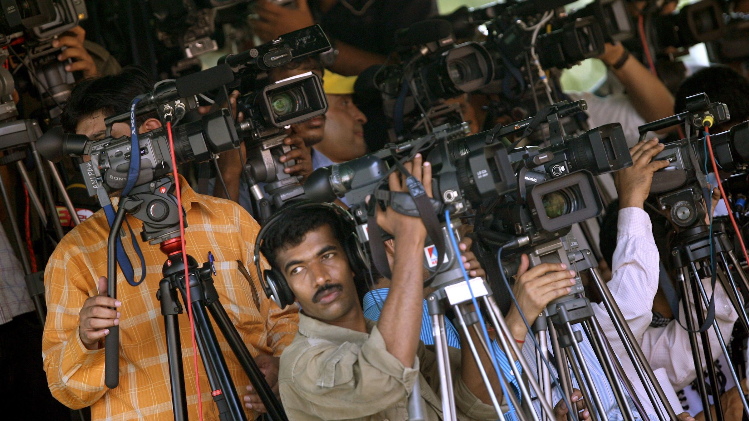 Television cameramen take pictures of India's Prime Minister Manmohan Singh, who is on his way to submit his resignation to President Pratibha Patil at the presidential palace in New Delhi May 18, 2009. The Congress-led coalition eyed possible new allies on Monday after a decisive general election victory raised hopes of a stable government and sent financial markets soaring. REUTERS/Arko Datta (INDIA POLITICS) - RTXIPKS