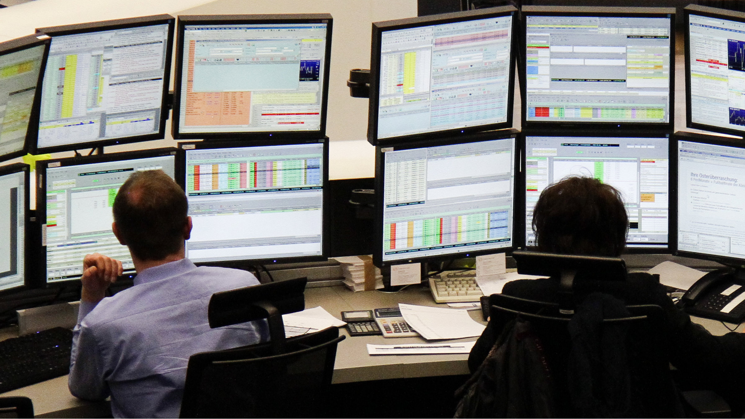 Traders are pictured at their desks at the Frankfurt stock exchange.