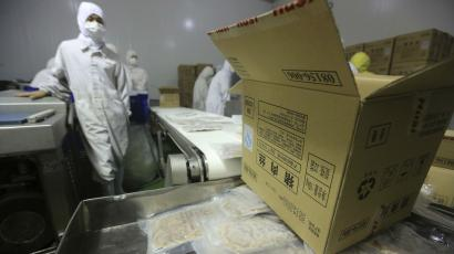 Employees work at a production line prior to a seizure conducted by officers from the Shanghai Food and Drug Administration, at the Husi Food factory in Shanghai, July 20, 2014. A watchdog closed Shanghai Husi Food Co Ltd, a local unit of OSI, and seized meat products suspected of being beyond their expiration date