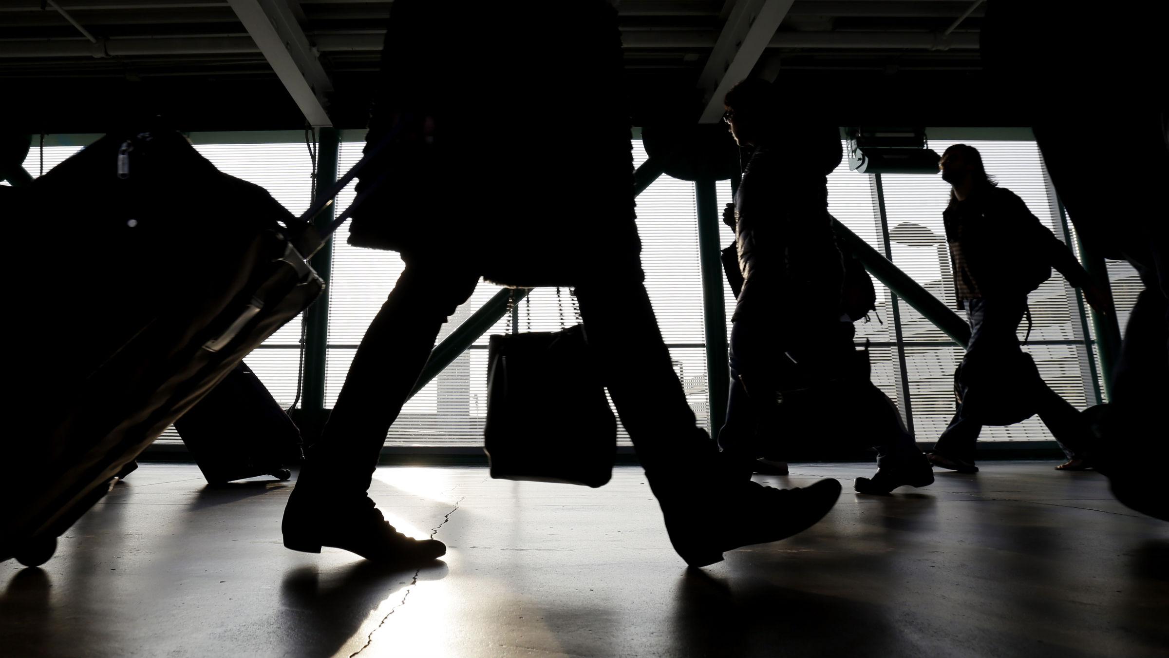 Silhouette of people walking in airport