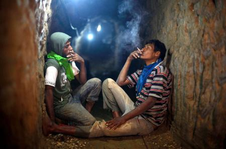Palestinian tunnel workers smoke cigarettes as they rest inside a smuggling tunnel flooded by Egyptian security forces, beneath the Gaza-Egypt border in the southern Gaza Strip September 10, 2013. Egyptian security forces have stepped up a crackdown campaign on smuggling tunnels on the border between Egypt and Gaza Strip since last July, Hamas officials said.