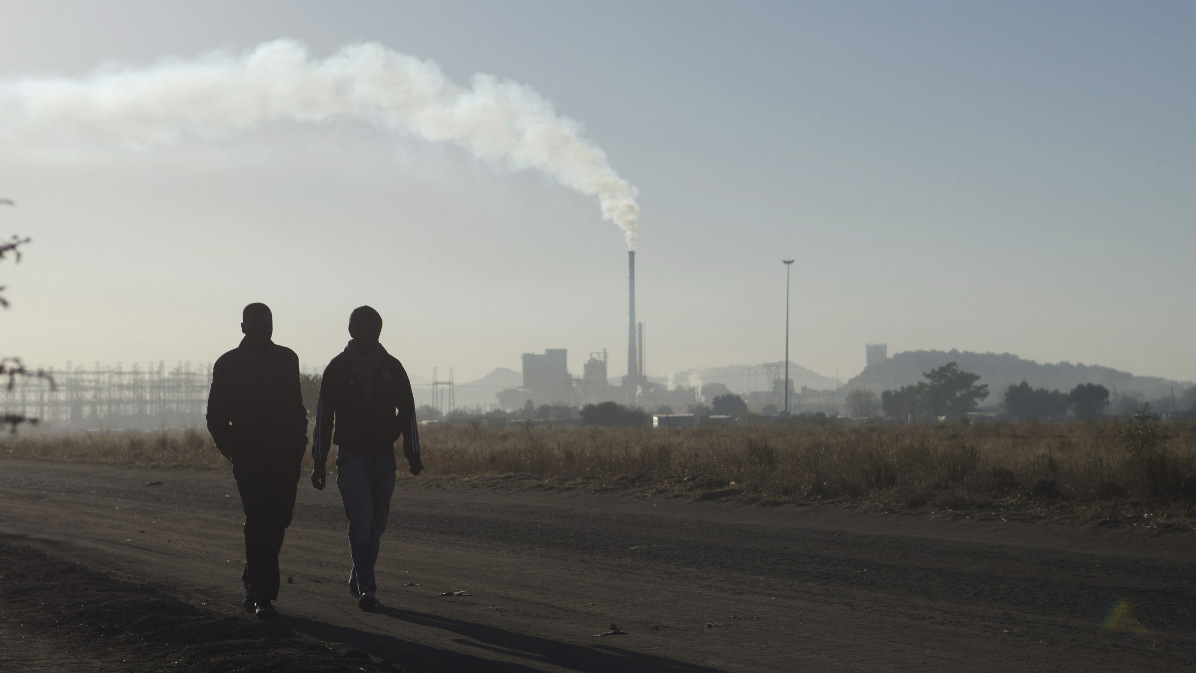 Workers walk past a Lonmin's Marikana platinum mine, June 24, 2014. Differences over possible job cuts in South Africa's platinum mines emerged on Tuesday as mining union AMCU prepared to sign a three-year wage deal with the world's top producers of the metal to end a crippling five-month strike. The Association of Mineworkers and Construction Union (AMCU) on Monday declared an end to the longest and costliest strike in South African history. REUTERS/Skyler Reid