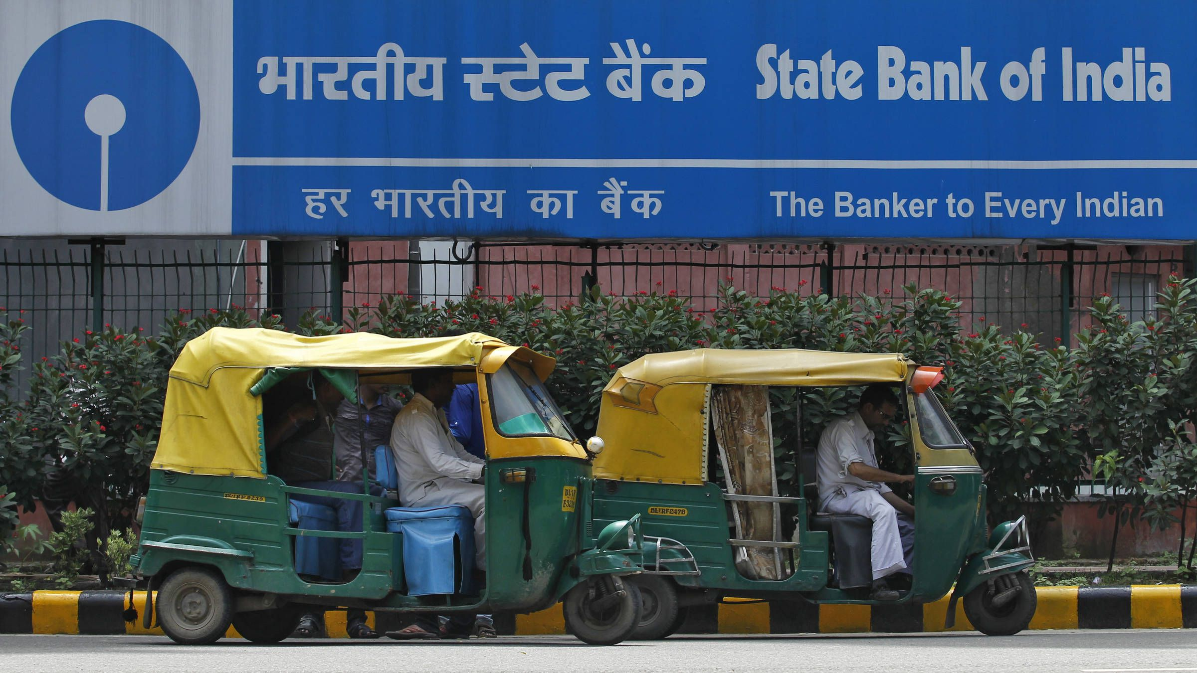 Auto rickshaws wait in front of the head office of State Bank of India (SBI) in New Delhi