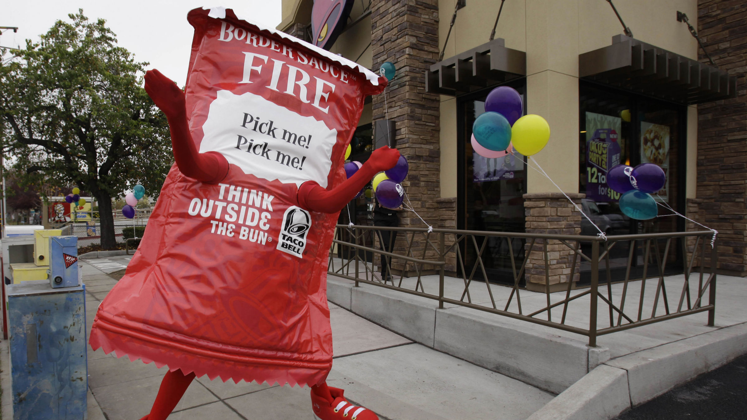 "This Dec. 13, 2010 photo shows a Taco Bell restaurant opening with a person in a taco sauce outfit outside in Mountain View, Calif. Taco Bell is launching an advertising campaign Friday to fight back against a lawsuit charging its taco filling isn't beef. A class-action lawsuit was filed late last week in federal court in California. It claimed Taco Bell falsely advertised its products as ""beef."" The suit alleges that the fast-food chain actually uses a meat mixture in its burritos and tacos that contains binders and extenders and does not meet requirements set by the U.S. Department of Agriculture to be labeled beef."