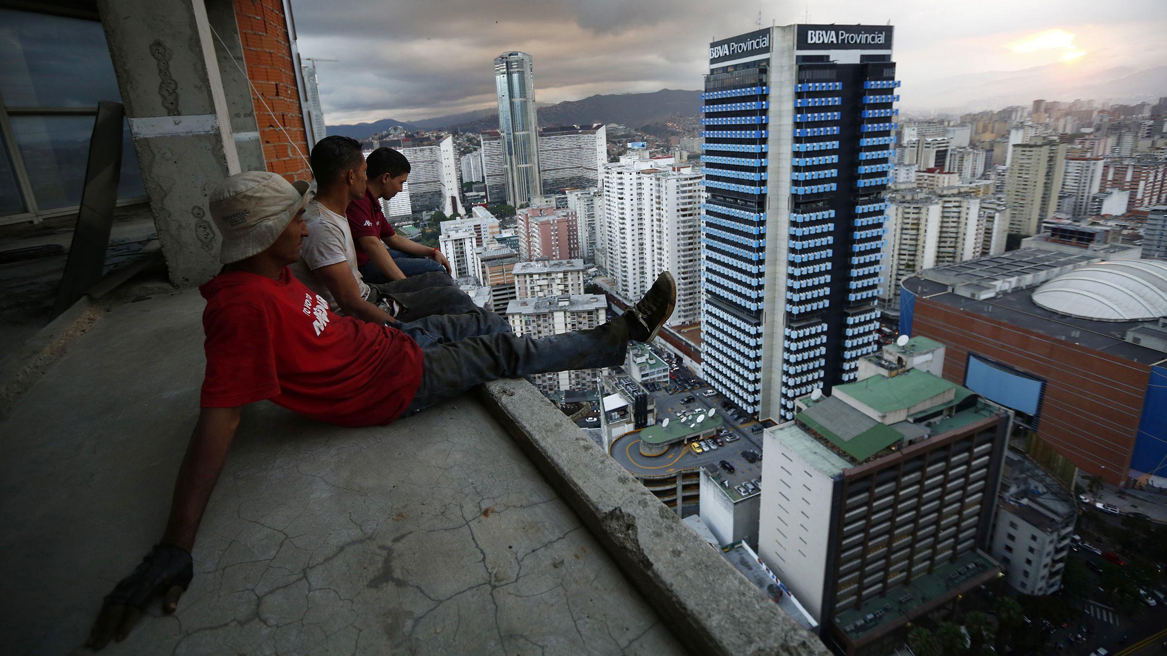 Men sitting on the edge of Caracas's vertical slum Torre David