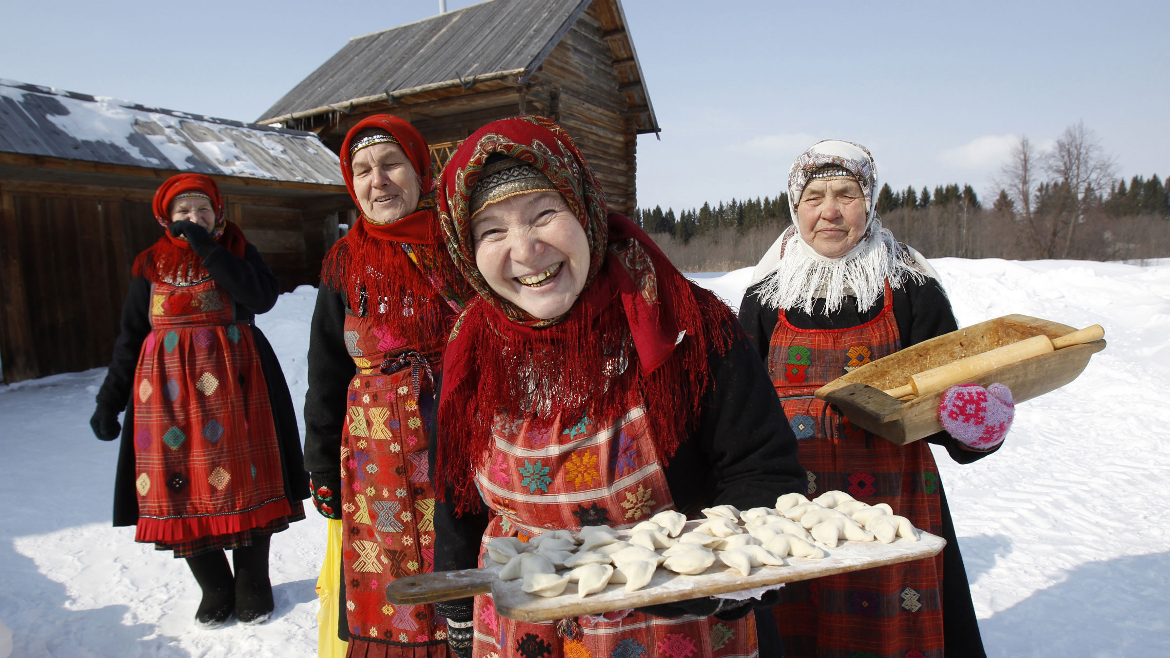 "Alevtina Byagisheva (2nd R), 54, Ekaterina Shklayeva (R), 74, Zoya Dorodova (2nd L), 74, and Granya Baisarova, 62, members of the singing group ""Buranovskiye Babushki"", offer home made dumplings at a folk museum near the village of Ludorvai in the central Russian region of Udmurtia March 16, 2012. A group of ladies ranging in age from 42 to 86 who sing traditional songs and pop classics in their own language have been voted by popular demand to represent Russia in the forthcoming Eurovision song contest. Picture taken March 16."