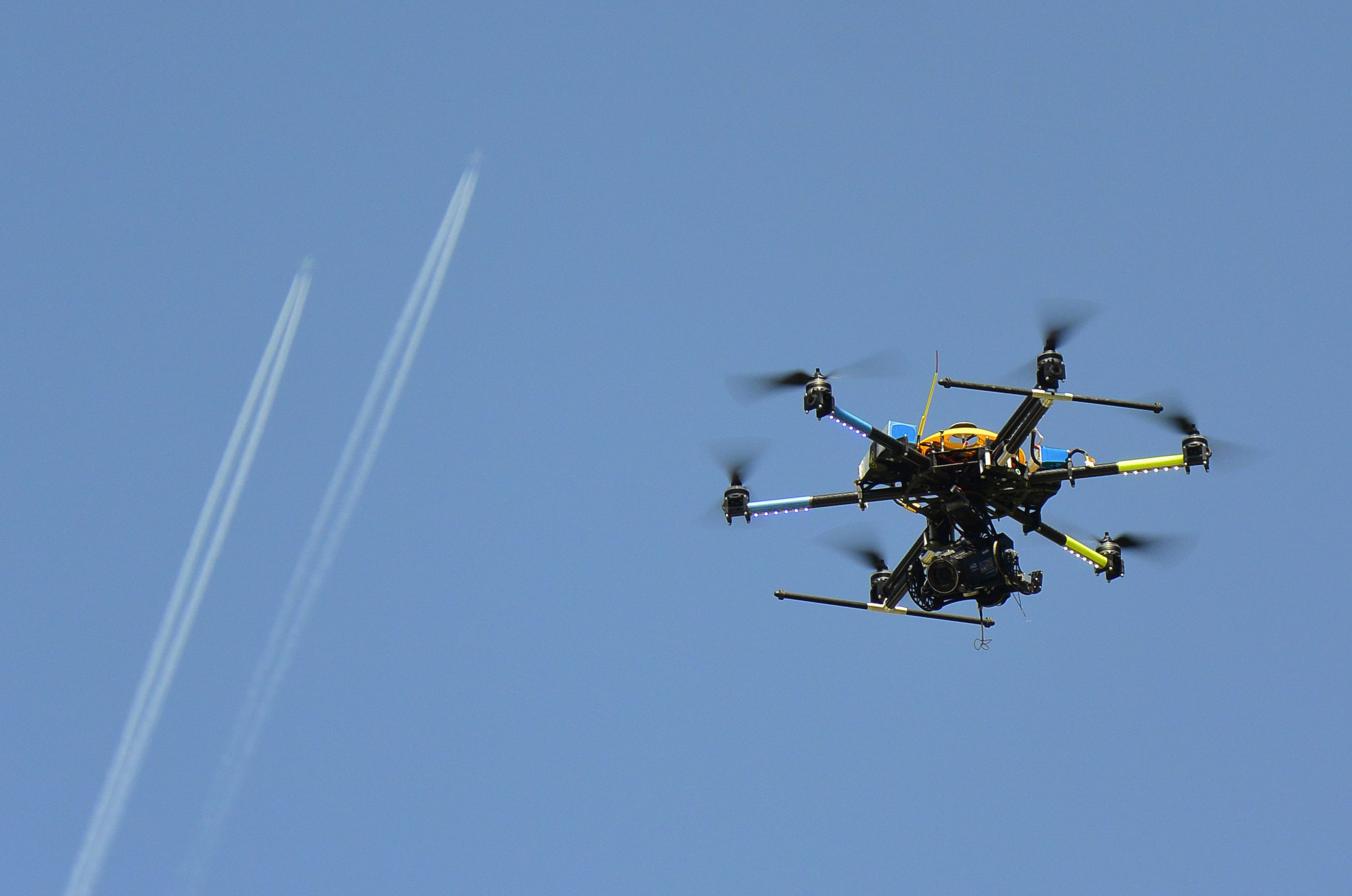An octocopter (a drone with eight rotors) hovers in front of vapour trails left by aircrafts during a presentation, to showcase the potential use of drones in the video and photography industries, in Pirnice, May 14, 2013.  REUTERS/Srdjan Zivulovic (SLOVENIA - Tags: TRANSPORT MEDIA SCIENCE TECHNOLOGY) - RTXZLX8