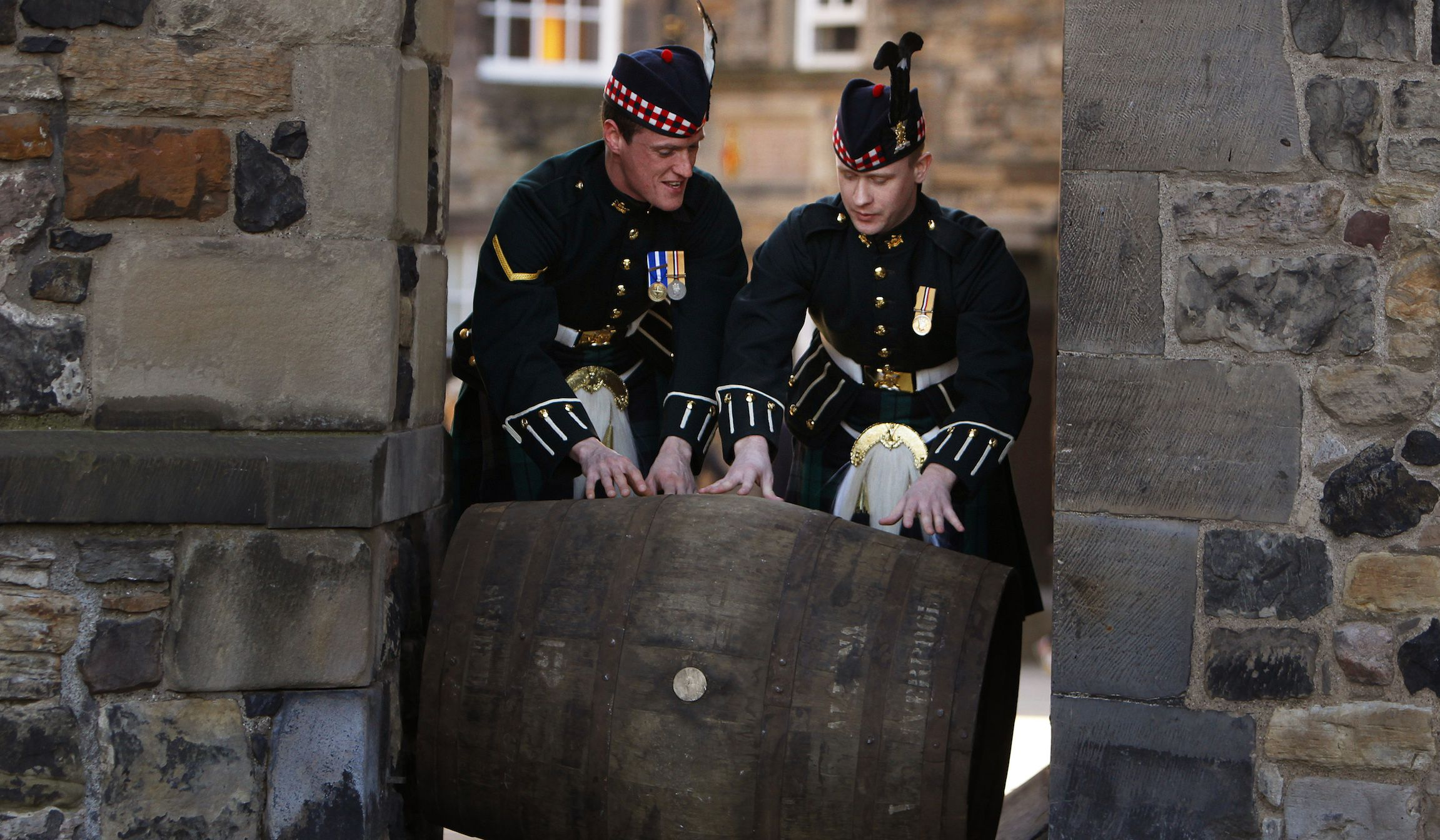 Lance Corpral Alan Leiper (L) and Private Kris Green push a wooden cask of Mortlach 70-year-old single malt whisky at Edinburgh castle in Scotland March 11, 2010. A 70cl bottle of the whisky, which is claimed to be the world's oldest single malt, sells for 10,000 pounds ($15,012) and the 20cl bottle sells for 2,500 pounds ($3753).  REUTERS/David Moir (BRITAIN - Tags: SOCIETY) - RTR2BIBI