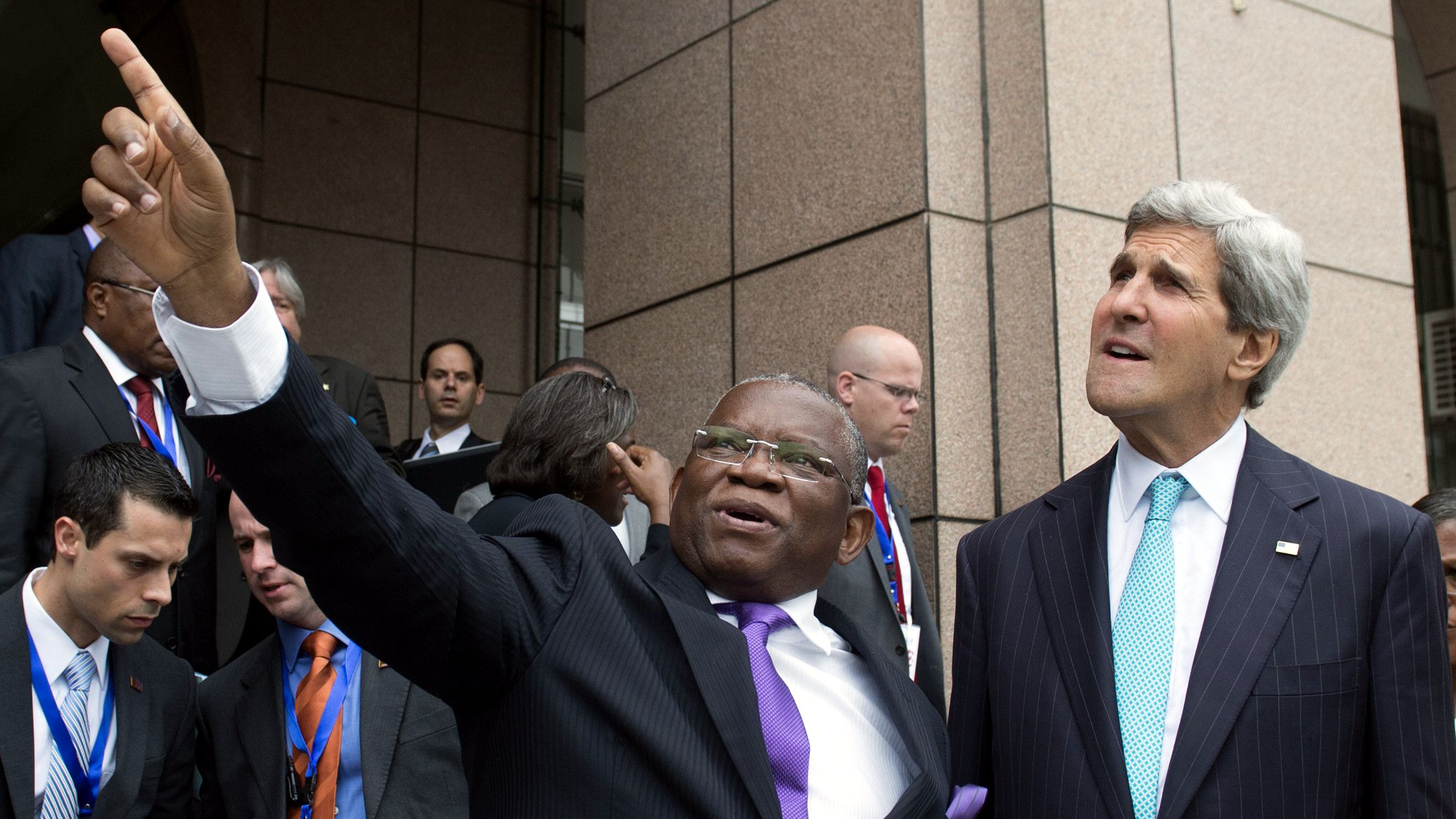 Foreign Minister Georges Rebelo Chicoti of Angola, left, shows US Secretary of State John Kerry nearby government buildings following meetings at the Ministry of Finance in Luanda, Angola, May 5, 2014. Kerry on May 4 praised oil-rich Angola's leadership role in efforts to solve long-drawn conflicts on the African continent.