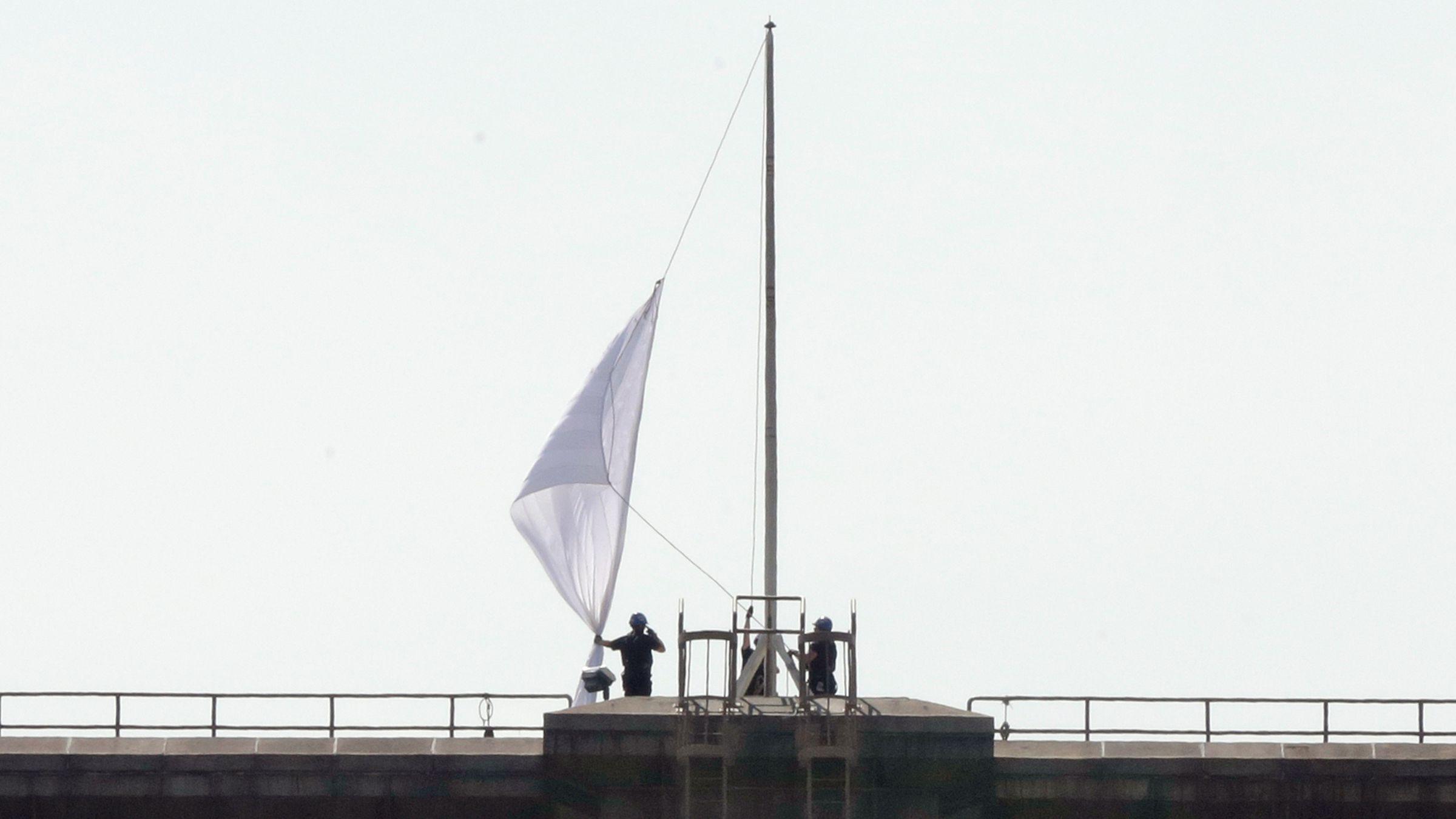A white flag set atop the Brooklyn Bridge as an art installation