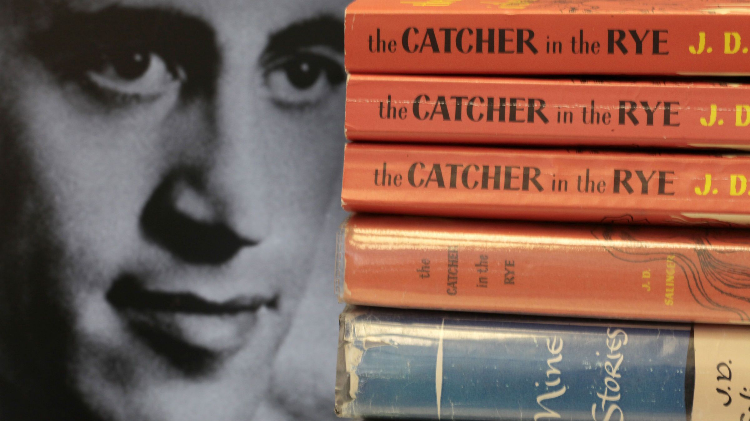 """FILE - In this Jan. 28, 2010 file photo, a photo of J.D. Salinger appears next to copies of his classic novel """"The Catcher in the Rye"""" as well as his volume of short stories called """"Nine Stories"""" at the Orange Public Library in Orange Village, Ohio. Salinger, died Jan. 27, 2010, in Cornish, N.H., at the age of 91. Letters written by Salinger to a spiritual mentor have been donated to the Morgan Library & Museum. The Morgan, based in Manhattan, announced Tuesday, April 9, 2013, that it will receive 28 letters by the author of """"The Catcher of the Rye."""" The letters were written to Swami Vivekananda, founder of the Ramakrishna-Vivekananda Center, which donated the correspondence. (AP Photo/Amy Sancetta, File)"""