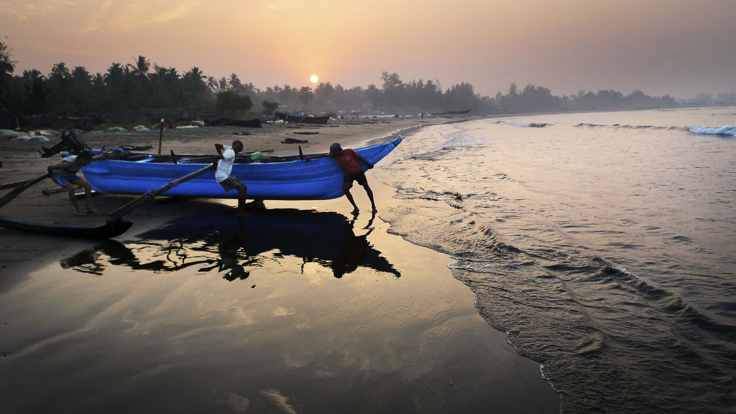 Indian fishermen push their boat ashore at sunrise after a night of fishing at Morjim beach in north Goa, on the Arabian Sea, southern India, Friday, March 12, 2010. (AP Photo/Kevin Frayer)