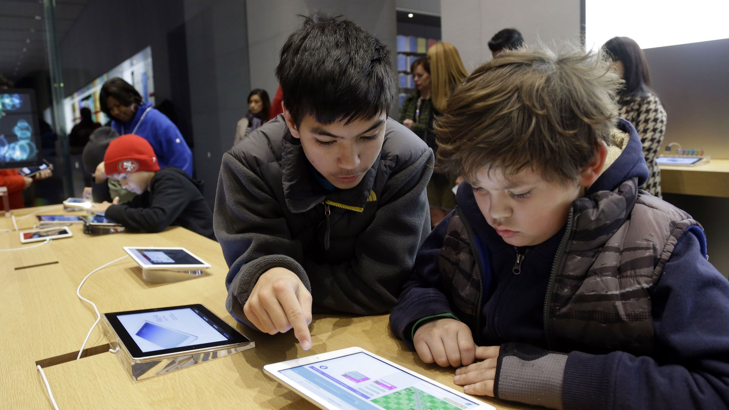 Matthew Triska, 13, center, helps Alex Fester, 10, to build code using an iPad at a youth workshop at the Apple store on Wednesday, Dec. 11, 2013, in Stanford, Calif. Apple stores nationwide were participating in computer science education week Wednesday, part of a joint effort with code.org to teach children the basics of coding. (AP Photo/Marcio Jose Sanchez)