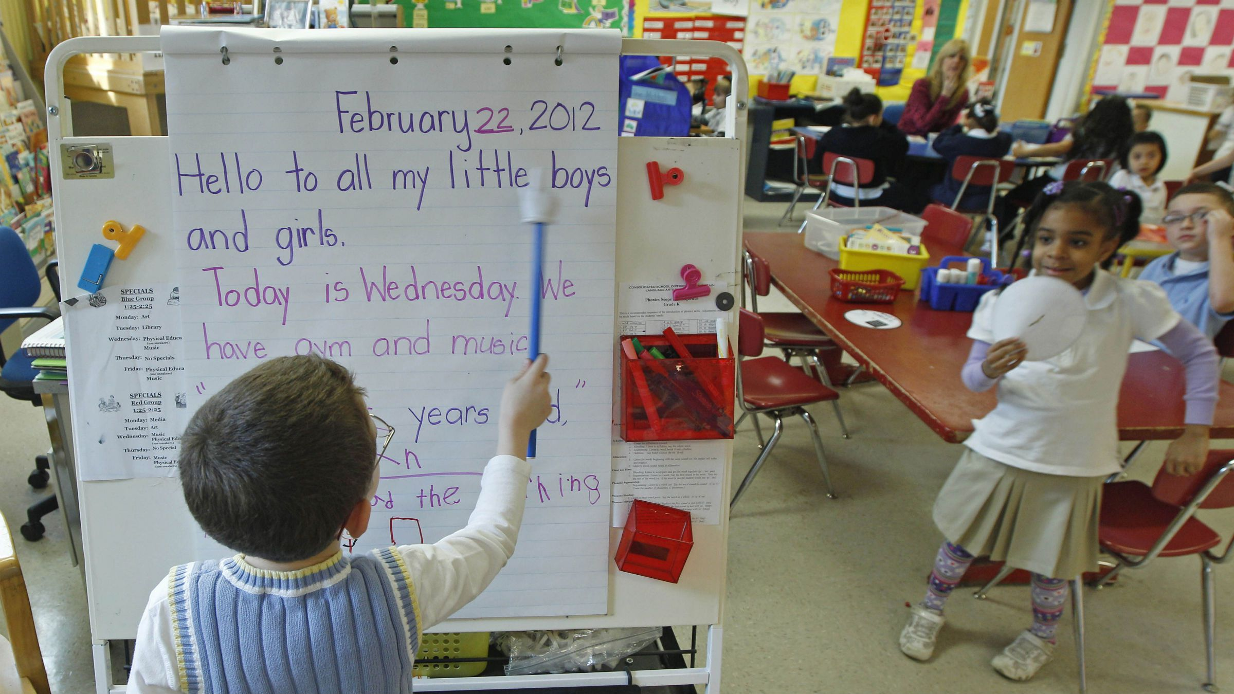 Ian Moore reads the daily message board in a kindergarten class at the Diloreto Magnet School in New Britain, Conn., Wednesday Feb. 22, 2012. As Connecticut lawmakers consider sweeping reforms intended to close the achievement gap between wealthy and poor school districts, another gap is growing: The disparity between communities that offer full-day kindergarten and those that don't. (AP Photo/Charles Krupa)
