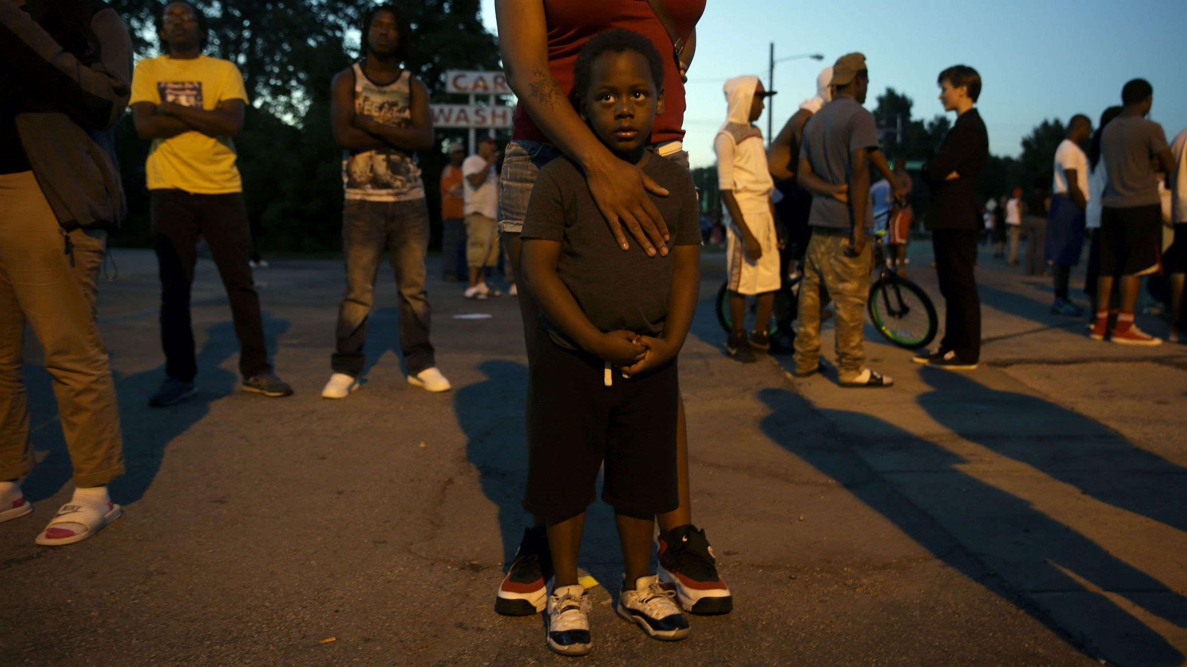 A black boy stands in Ferguson