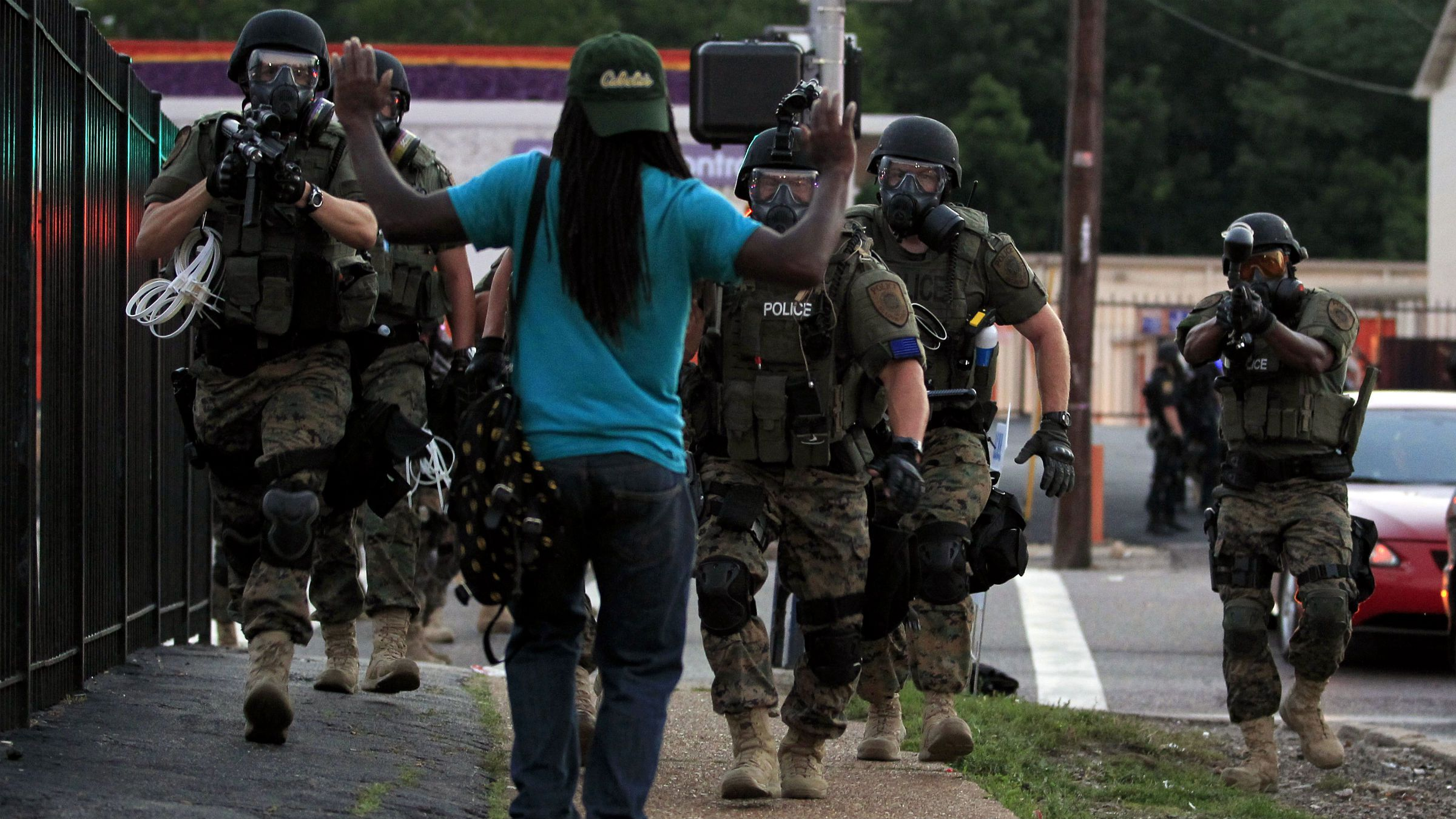 Police wearing riot gear walk toward a man with his hands raised Monday, Aug. 11, 2014, in Ferguson, Mo. Authorities have made several arrests in Ferguson, where crowds have looted and burned stores, vandalized vehicles and taunted police after a vigil for an unarmed black man who was killed by police. (AP Photo/Jeff Roberson)