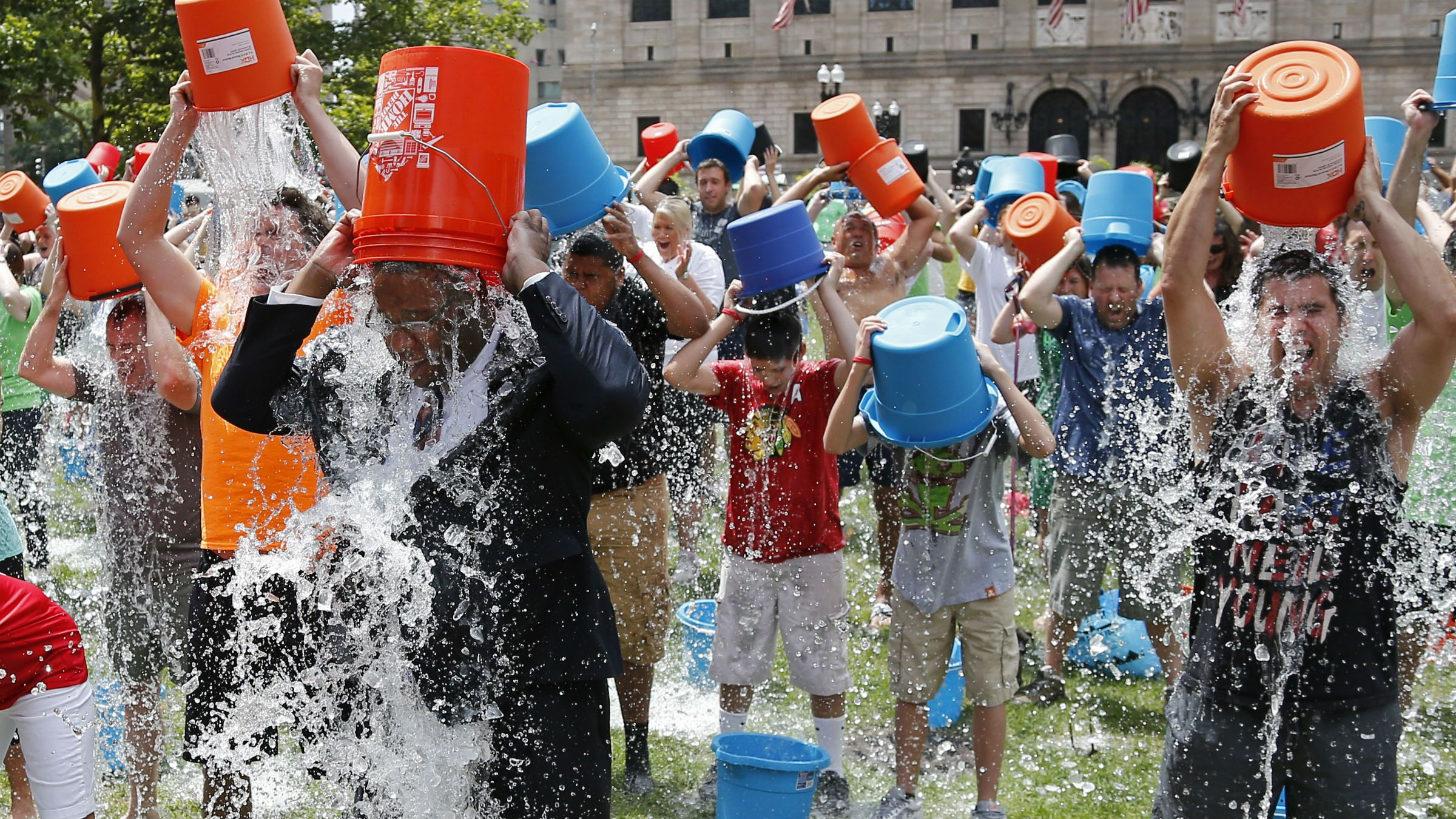 Boston City Councillor Tito Jackson, left in suit, leads some 200 people in the ice bucket challenge at Boston's Copley Square, Thursday, Aug. 7, 2014 to raise funds and awareness for ALS.The idea is easy: Take a bucket of ice water, dump it over your head, video it and post it on social media. Then challenge your friends, strangers, even celebrities to do the same within 24 hours or pay up for charity. (AP Photo/Elise Amendola)
