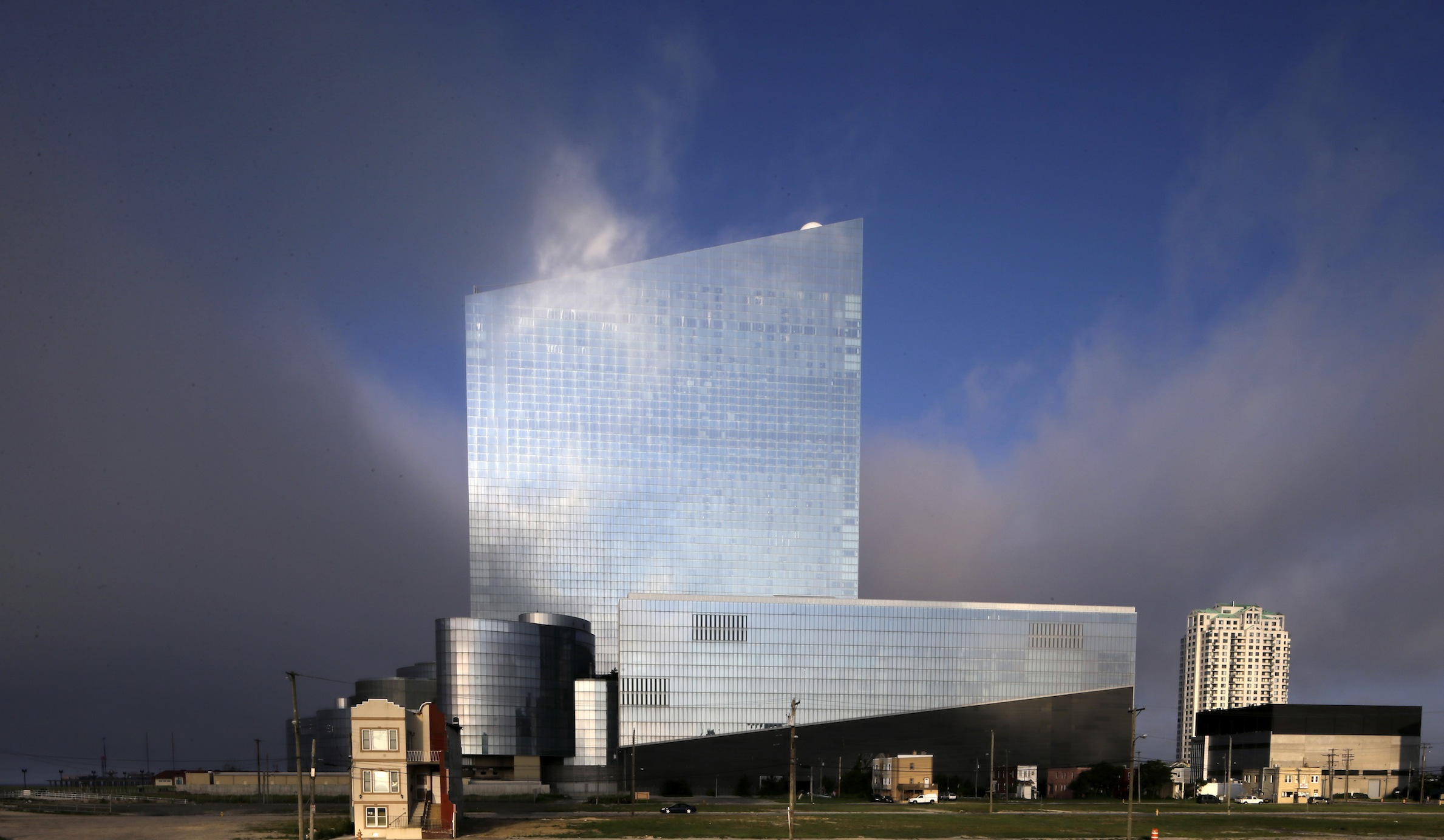 The last old home on a block, left, is seen near the Revel hotel and casino early Wednesday, July 23, 2014, in Atlantic City, N.J. (AP Photo/Mel Evans)