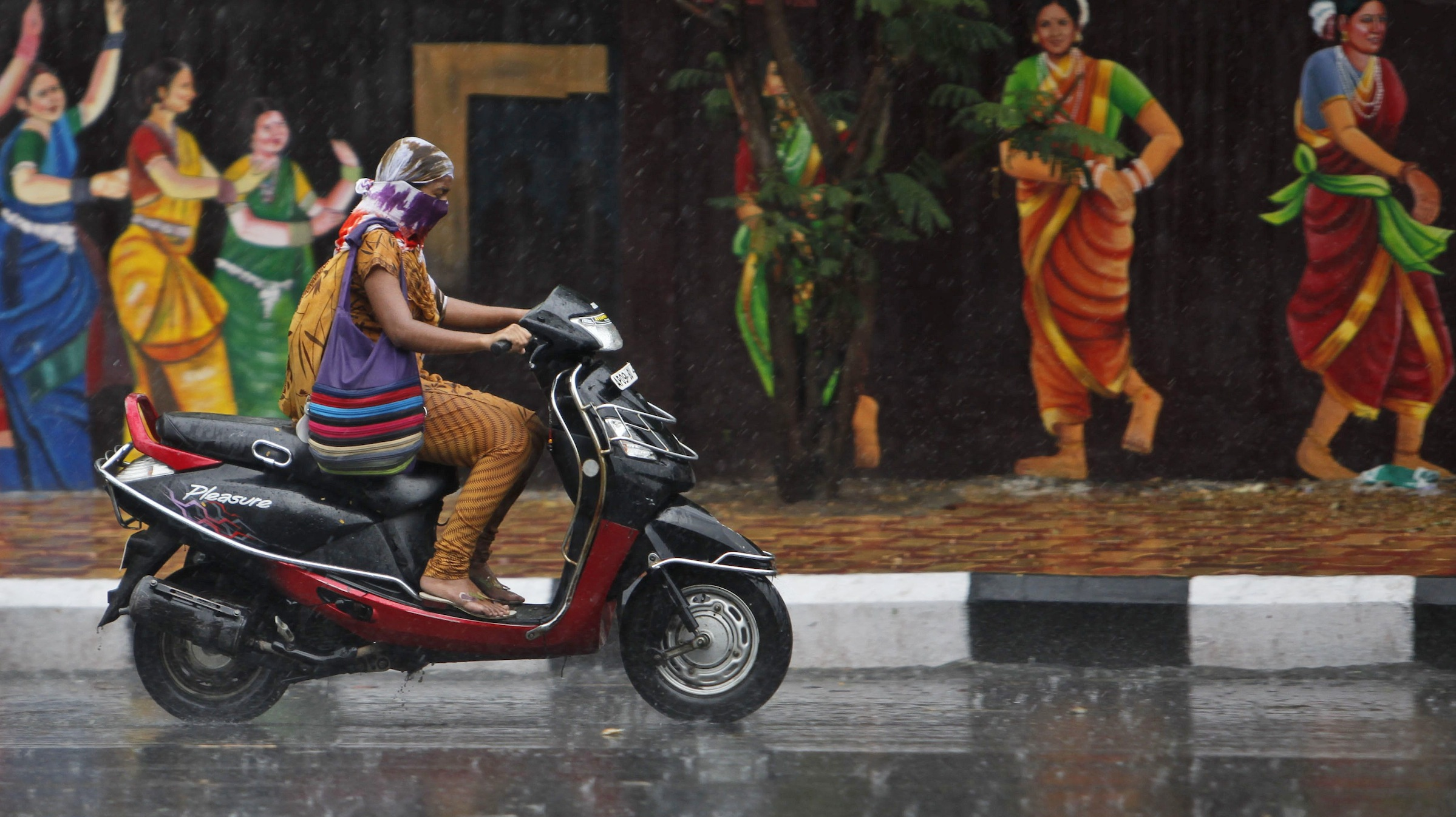 An Indian women rides a scooter during a sudden shower in Hyderabad, India, Tuesday, April 23, 2013. (AP Photo/Mahesh Kumar A.)
