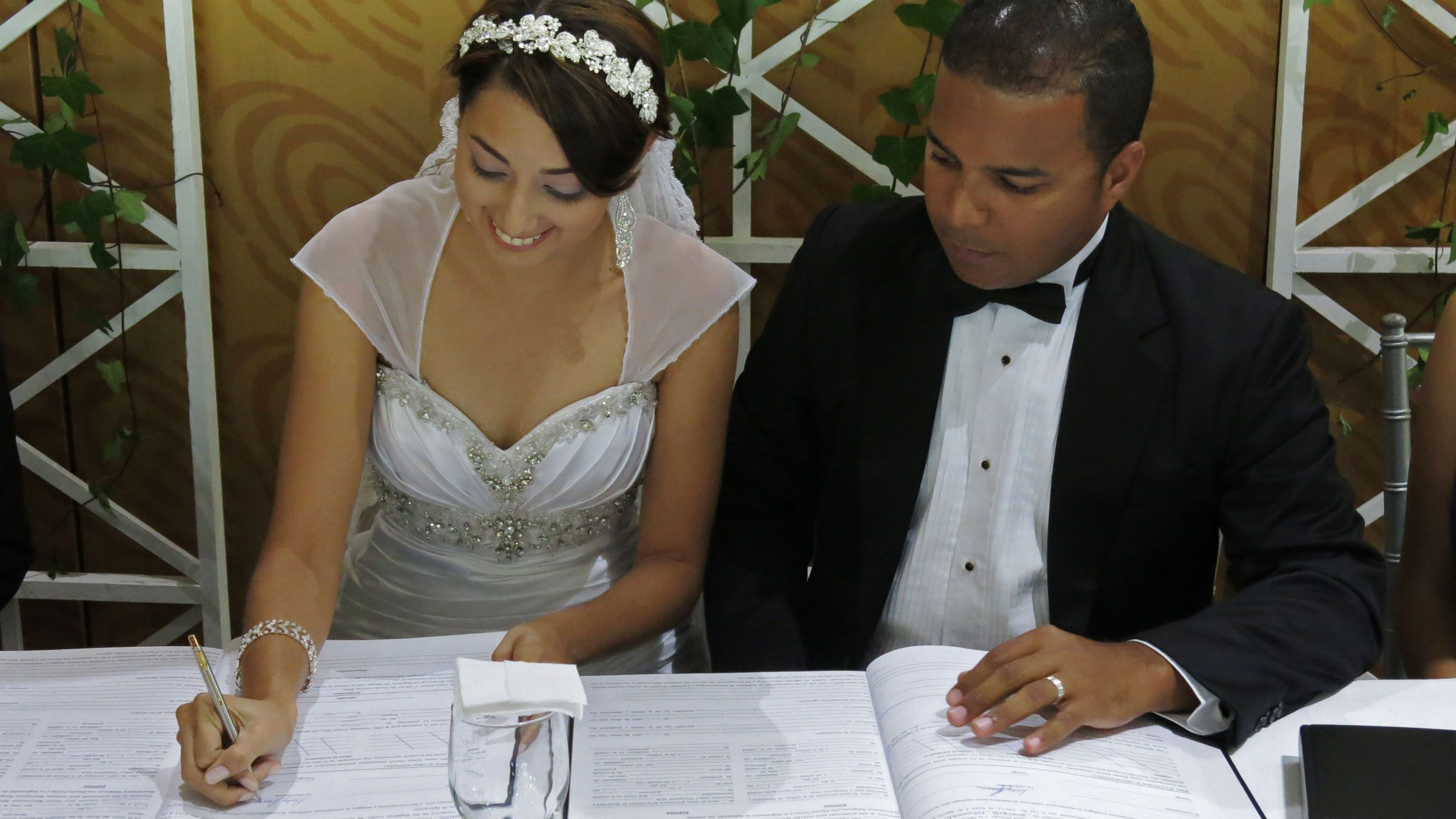 Bride Leidy Laura Cabreja signs a marriage license as her groom Baldwin Rodriguez looks on during their Jehovah's Witness wedding ceremony in Santo Domingo, Dominican Republic, Wednesday, Aug. 28, 2013. The couple became the first pair to marry under a new law recognizing religious weddings not held in a Roman Catholic church. Previously, marriages received legal recognition only if held at the civil registry or in a Catholic ceremony. (AP Photo/Ezequiel Abiu Lopez)