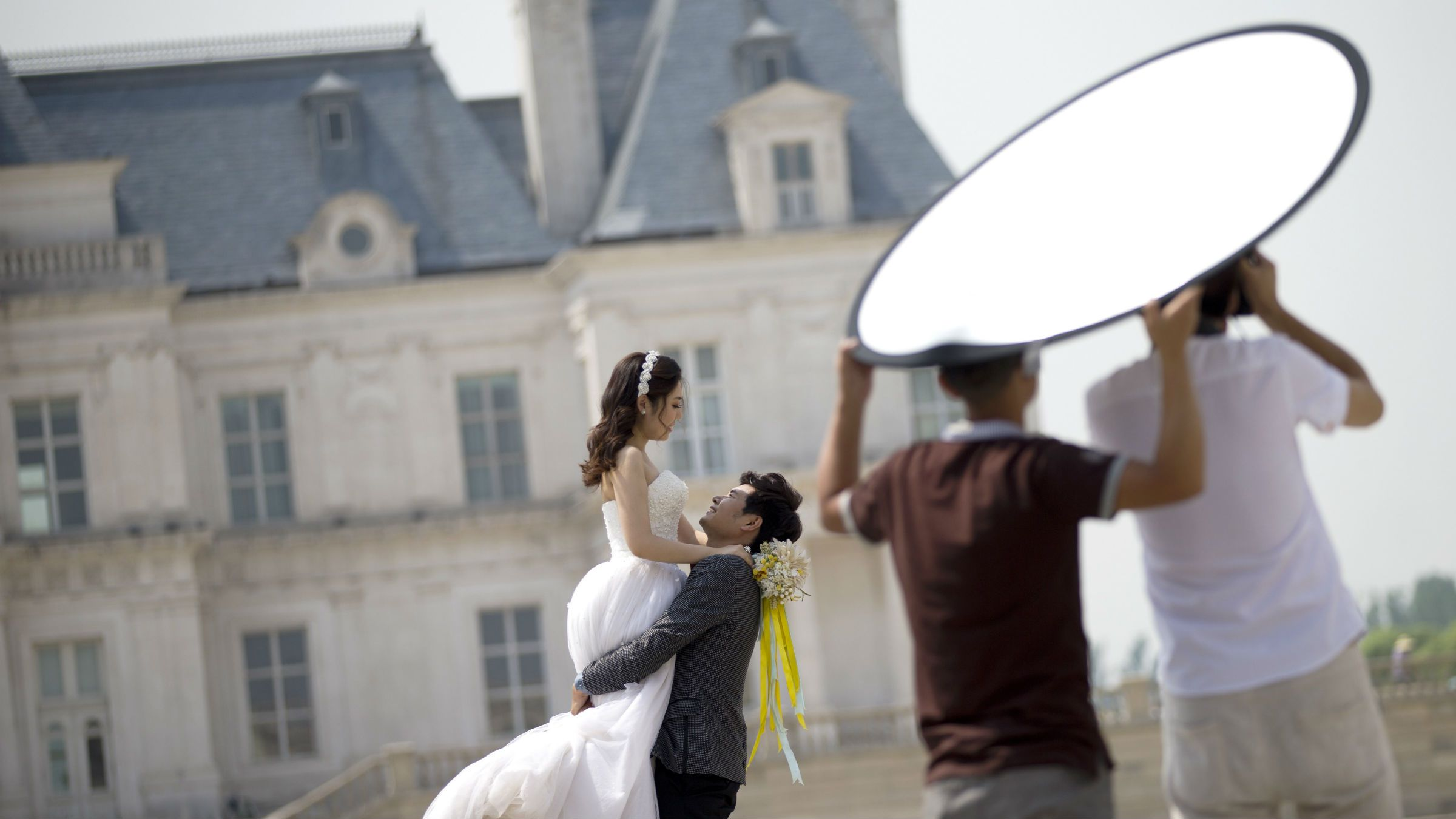 A groom lifts up his bride as they pose for wedding photos in front of the Laffitte Castle Hotel in Changping District, on the outskirts of Beijing, China Tuesday, June 24, 2014. Laffite Hotel was built on the model of Chateau de Maison-Laffitte in France. The building, majestic and luxurious replica of the Fontainebleau Palace in Paris, is a popular scenic spot as many newly wed couples visit for their wedding photos. (AP Photo/Andy Wong)