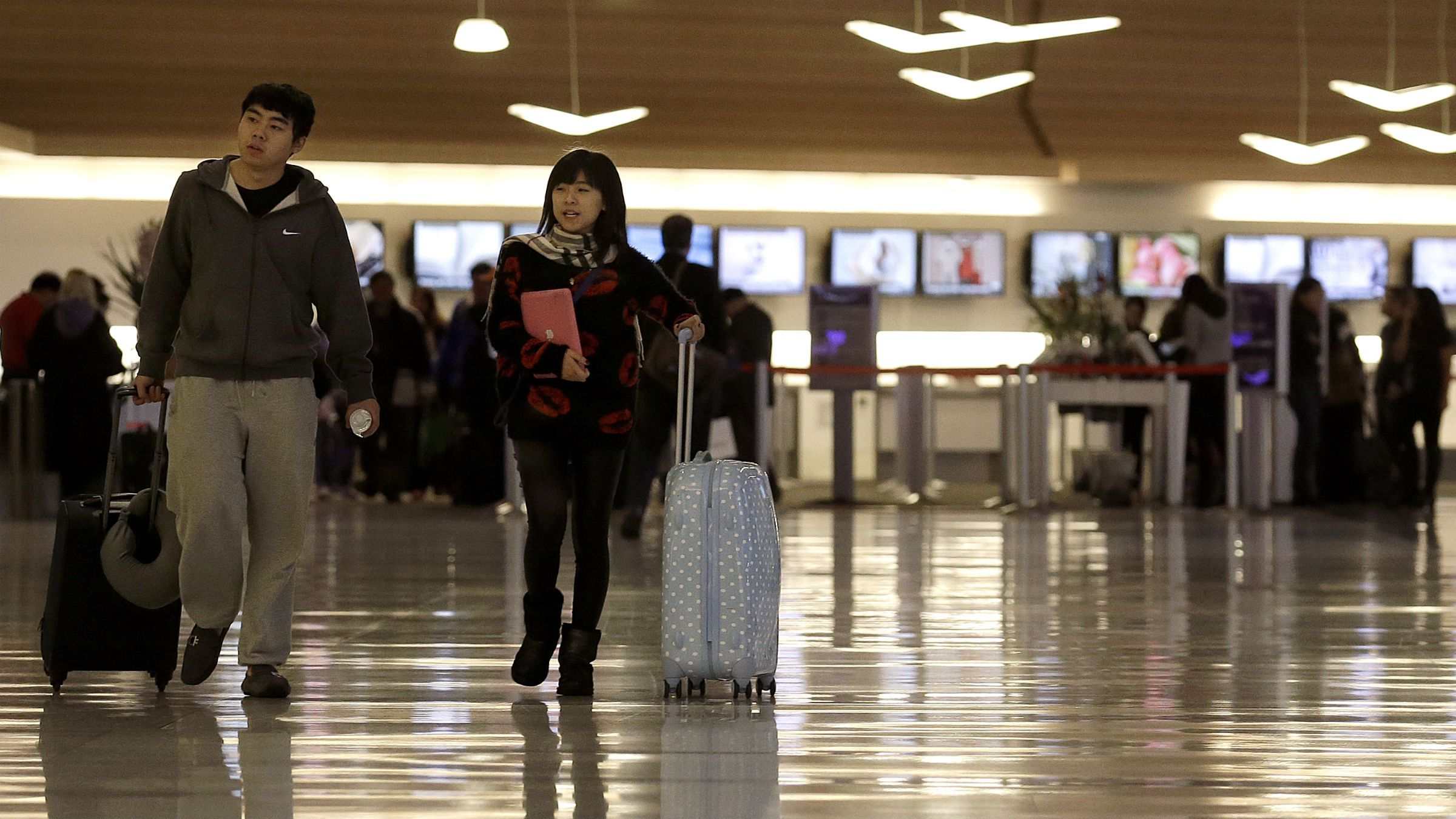 A man and woman walk through the domestic terminal at San Francisco International Airport in San Francisco, Thursday, Nov. 28, 2013. More than 43 million people are to travel over the long holiday weekend, according to AAA. (AP Photo/Jeff Chiu)