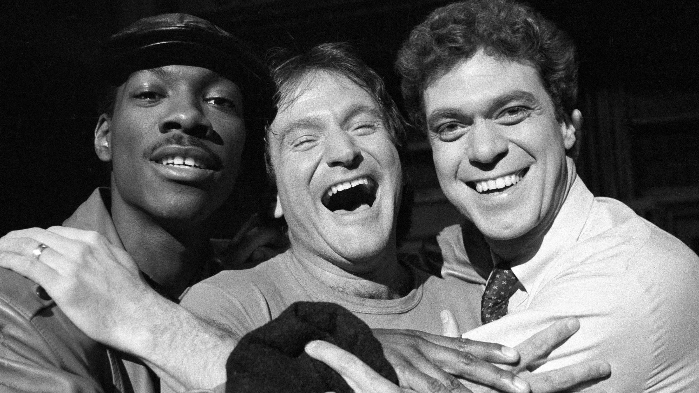 Robin Williams, center, takes time out from rehearsal at NBC's Saturday Night Live with cast members Eddie Murphy, left, and Joe Piscopo, Feb. 10, 1984. Williams will appear as guest host on the show. (AP Photo/Suzanne Vlamis)