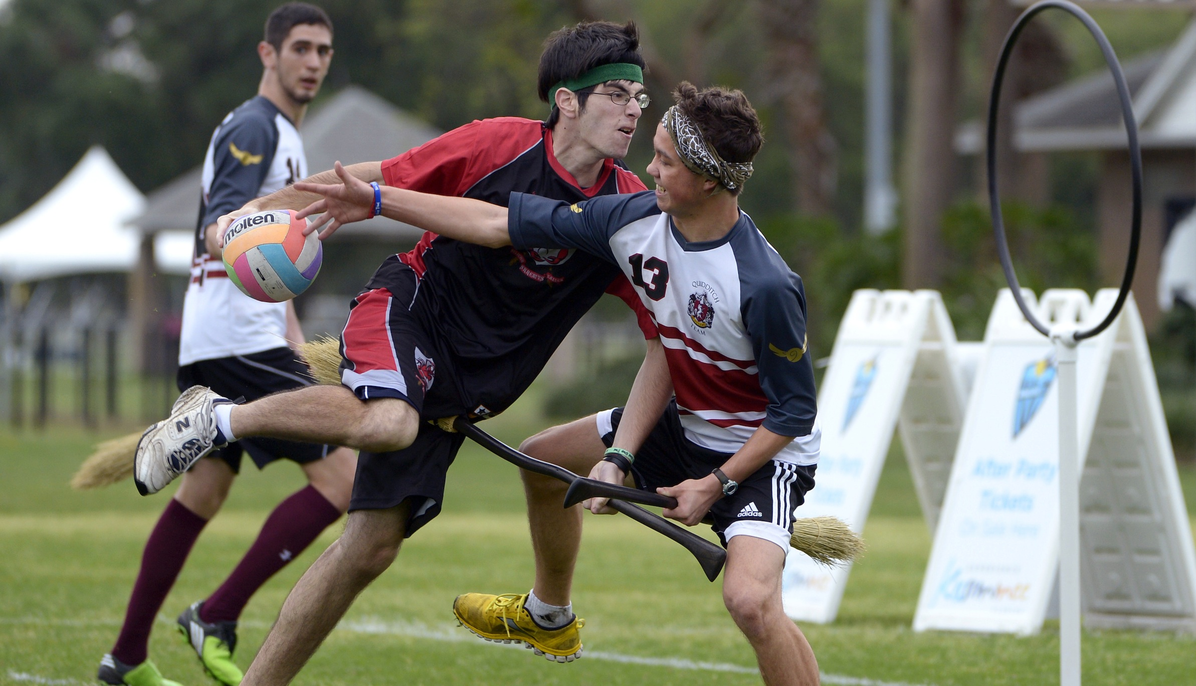Silicon Valley Skrewts' Logan Anbinder, center, drives to the goal between the University of Ottawa Quidditch team's Matthew Bunn, right, and Ahmed Al-Slaq during a scrimmage at the Quidditch World Cup in Kissimmee, Fla., Friday, April 12, 2013.  Quidditch is a game born within the pages of Harry Potter novels, but in recent years it's become a real-life sport.  The game is a co-ed, full contact sport that combines elements of rugby, dodgeball and Olympic handball. (AP Photo/Phelan M. Ebenhack)