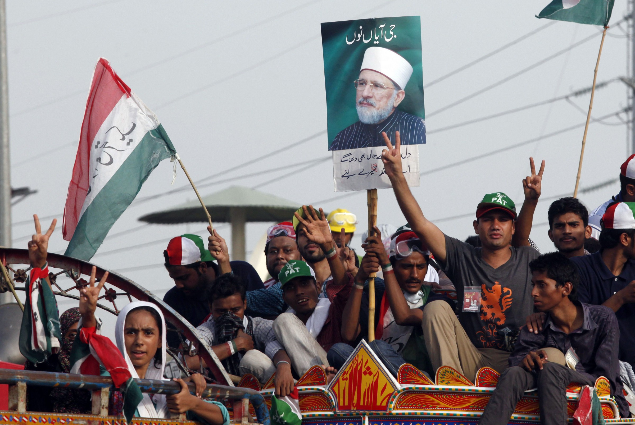 Supporters of Muhammad Tahirul Qadri, Sufi cleric and leader of political party Pakistan Awami Tehreek (PAT) gesture as they begin their march toward the capital from Lahore August 14, 2014. Thousands of anti-government protesters began to march on the Pakistani capital, Islamabad, on Thursday from the eastern city of Lahore, raising fears about political stability and prospects for civilian rule in the nuclear-armed country. Two protest groups - one led by cricketer-turned-opposition politician Imran Khan, and the other by activist cleric Tahir ul-Qadri - are heading to the capital to demand that a government they condemn as corrupt steps down. REUTERS/Mohsin Raza (PAKISTAN - Tags: POLITICS CIVIL UNREST) - RTR42FAZ