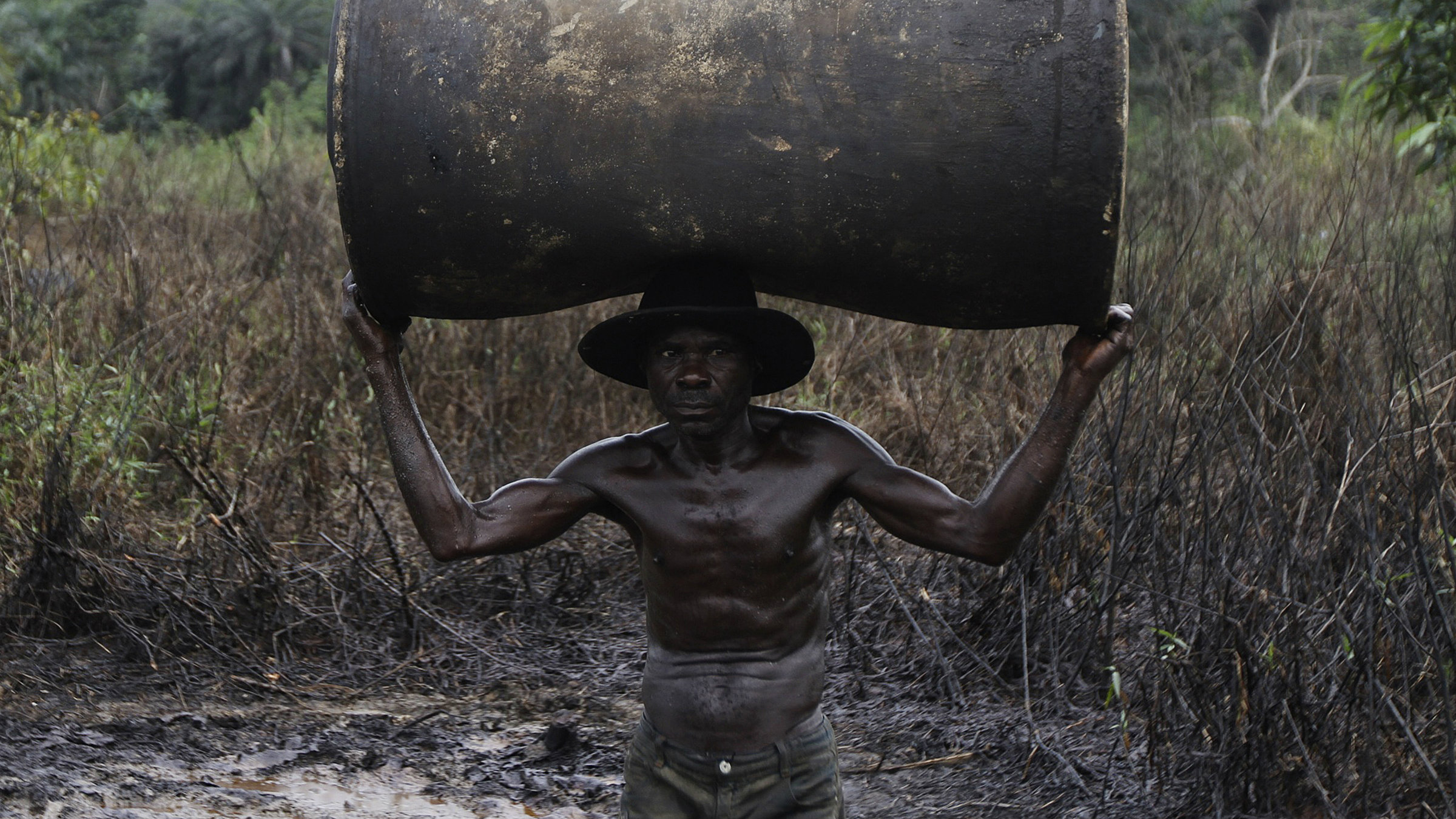 In Bayelsa state, Nigeria, a man carries an empty oil drum to be filled for sale later.