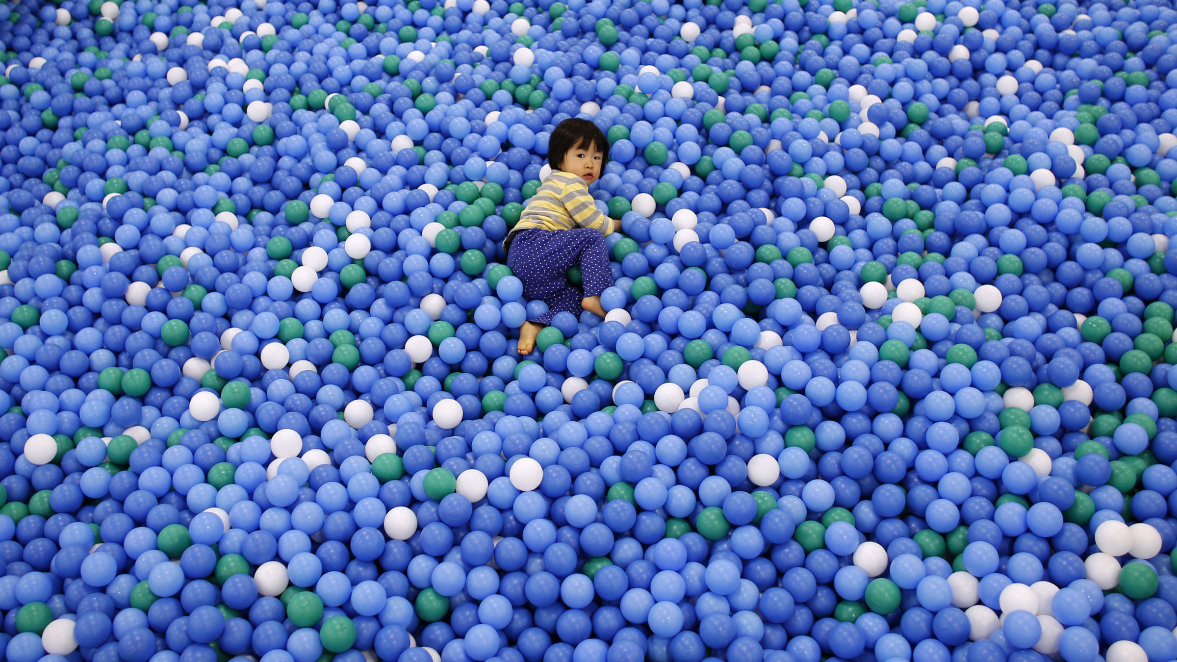 Two-year-old Nao Watanabe plays in a ball pit at an indoor playground which was built for children and parents who refrain from playing outside because of concerns about nuclear radiation in Koriyama, west of the tsunami-crippled Fukushima Daiichi nuclear power plant, Fukushima prefecture February 27, 2014. March 11 marks the third anniversary of the earthquake and tsunami that devastated Japan's Fukushima Daiichi nuclear power plant. In Koriyama, a short drive from the crippled Fukushima nuclear plant, the city recommended shortly after the disaster that children up to two years old not spend more than 15 minutes outside each day. Those aged 3 to 5 should limit their outdoor time to 30 minutes or less. The limits were lifted last year, but many kindergartens and nursery schools continue to obey them even now in line with the wishes of worried parents. An annual survey by the Fukushima prefecture Board of Education found that children in Fukushima weighed more than the national average in virtually every age group. The cause seems to be a lack of exercise and outdoor activity. Picture taken February 27, 2014.