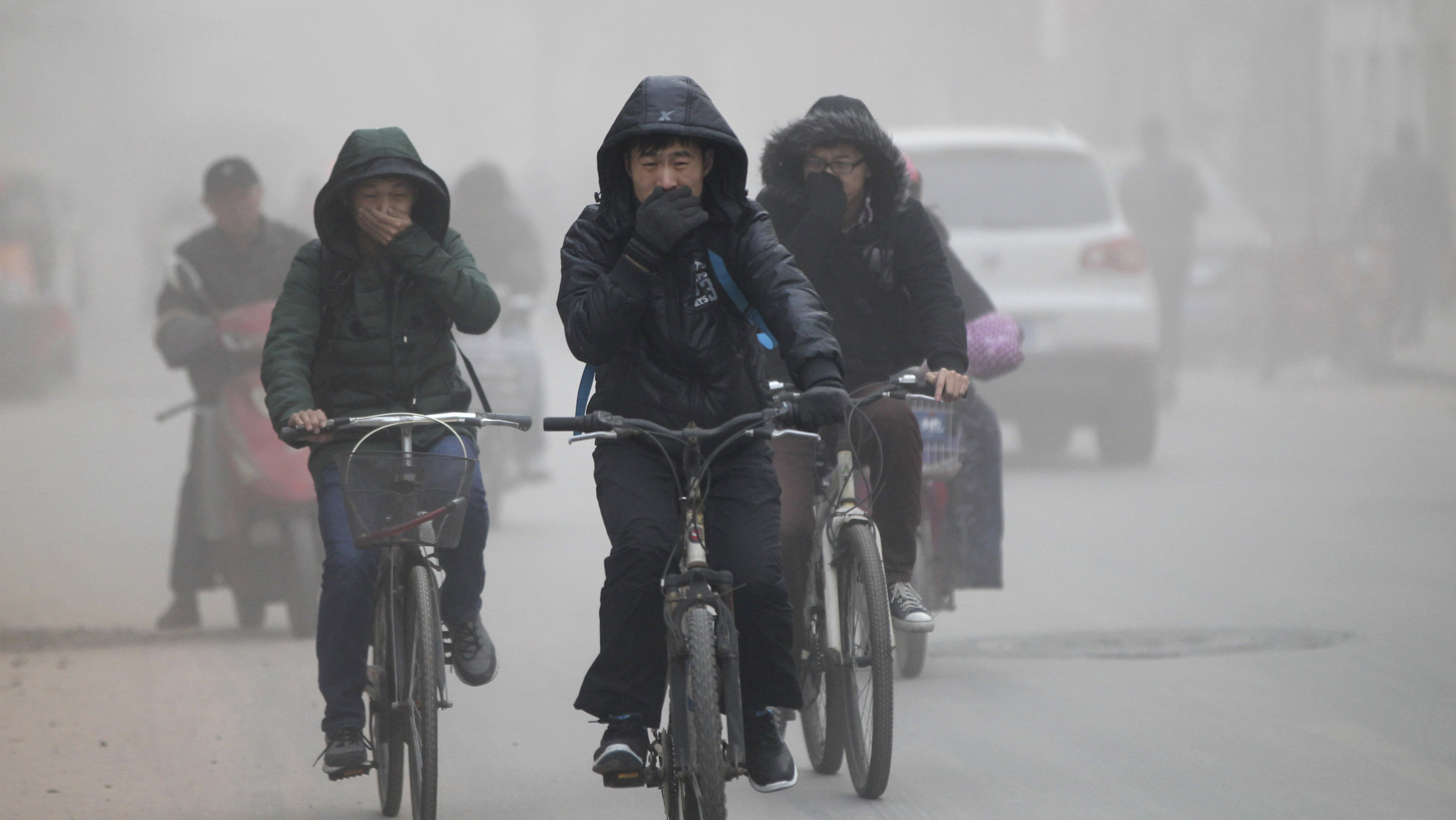 Residents cover their face from dust as they ride their bicycles along a street on a hazy day in Zhengzhou, Henan province December 10, 2013.  REUTERS/Stringer