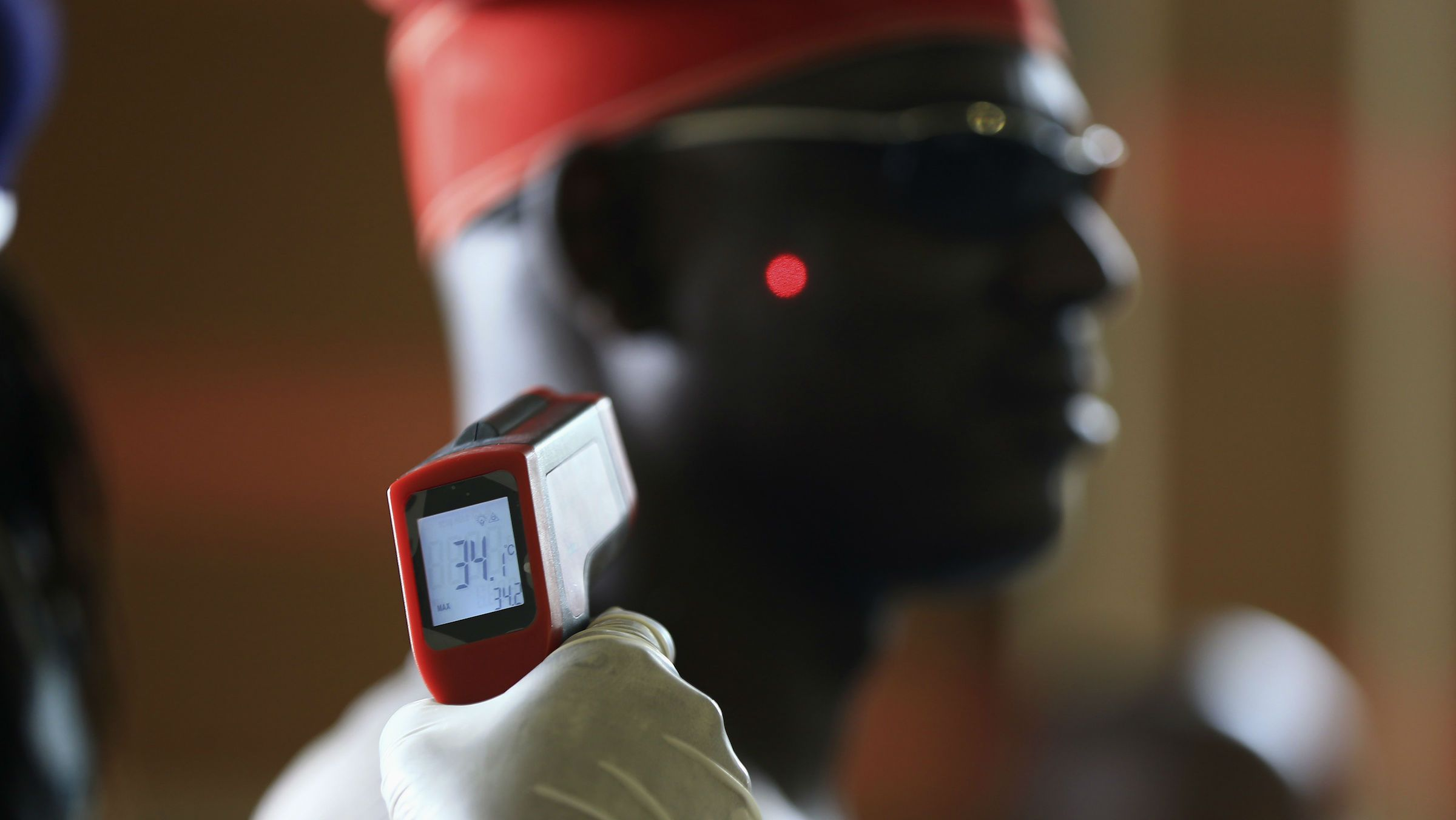 A man has his temperature taken using an infrared digital laser thermometer at the Nnamdi Azikiwe International Airport in Abuja, Nigeria.