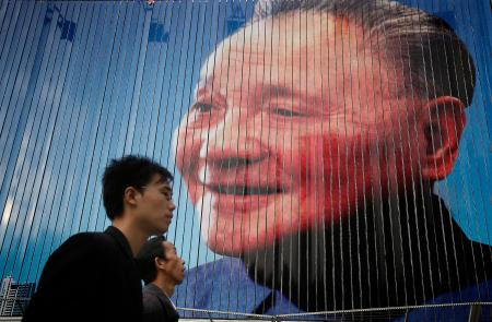 Men walk past a billboard featuring the late Chinese leader Deng Xiaoping, also known as the father of modern China, Thursday, Oct. 21, 2010 in Shanghai, China. China's rapid growth slowed in the latest quarter as Beijing steered its expansion to a more sustainable level, possibly cutting its contribution to a global recovery. (AP Photo/Eugene Hoshiko)