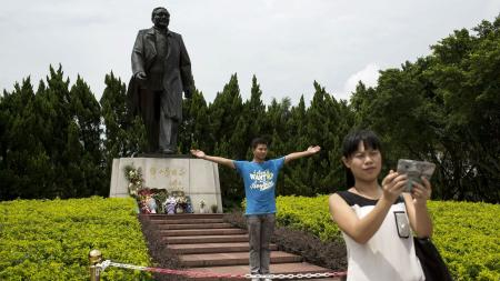Visitors pose in front of a statue of the late Chinese leader Deng Xiaoping in Shenzhen, in southern China's Guangdong province, August 19, 2014.