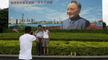 A couple poses in front of a billboard of Deng Xiaoping.