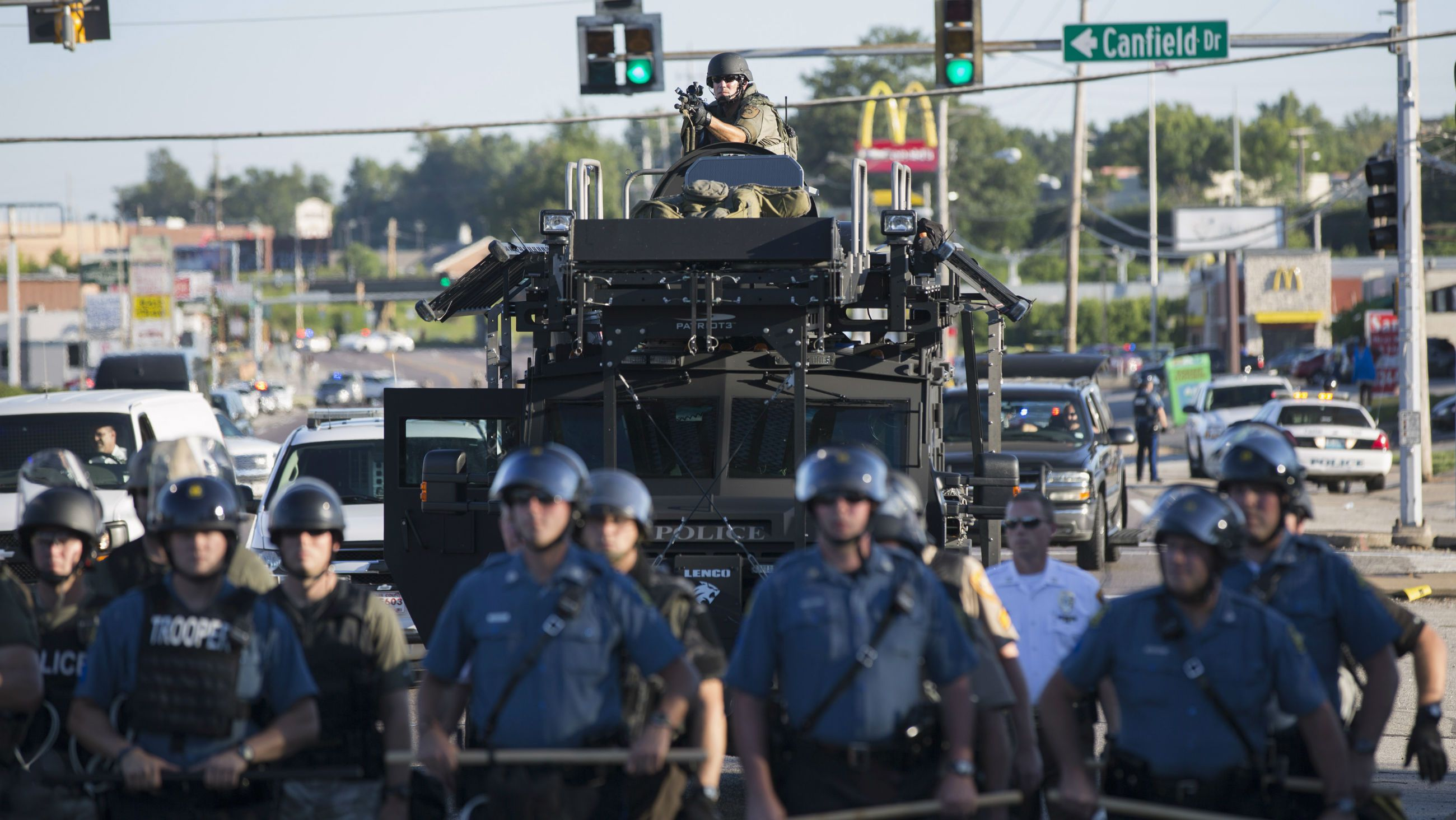 Riot police stand guard as demonstrators protest the shooting death of teenager Michael Brown in Ferguson, Missouri August 13, 2014. A McDonald's can be seen in the background.