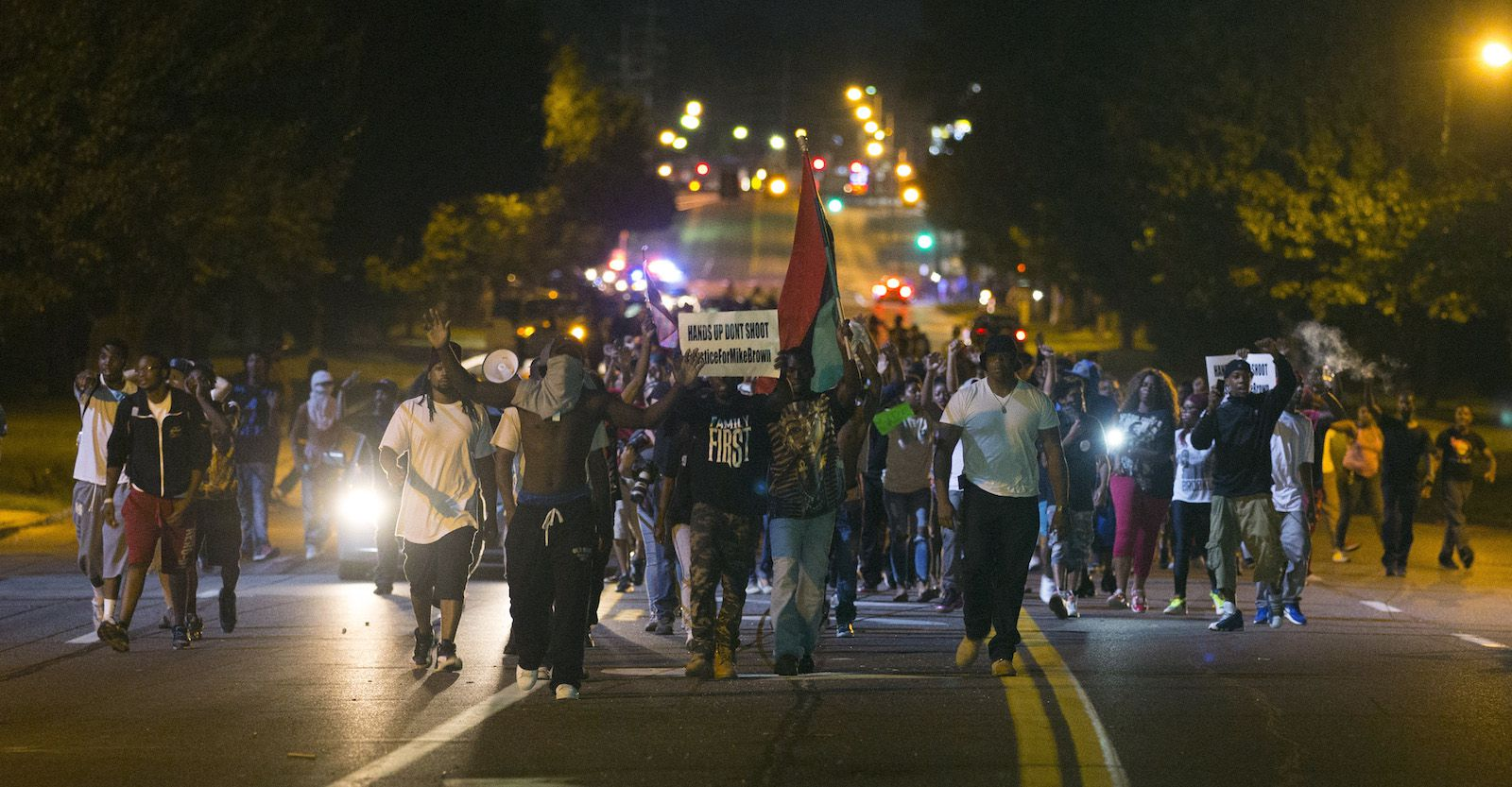 Demonstrators march in the street while protesting the shooting death of black teenager Michael Brown in Ferguson, Missouri August 12, 2014. Police said Brown, 18, was shot in a struggle with a gun in a police car but have not said why Brown was in the car. At least one shot was fired during the struggle and then the officer fired more shots before leaving the car, police said. But a witness to the shooting interviewed on local media has said that Brown had been putting his hands up to surrender when he was killed. The FBI has opened a civil rights investigation into the racially charged case and St. Louis County also is investigating.  REUTERS/Mario Anzuoni  (UNITED STATES - Tags: CRIME LAW TPX IMAGES OF THE DAY) - RTR42841