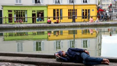 A man sleeps along the Canal Saint Martin during a hot summer day in Paris July 16, 2014. REUTERS/Charles Platiau (FRANCE - Tags: SOCIETY TRAVEL ENVIRONMENT TPX IMAGES OF THE DAY) - RTR3YWGD