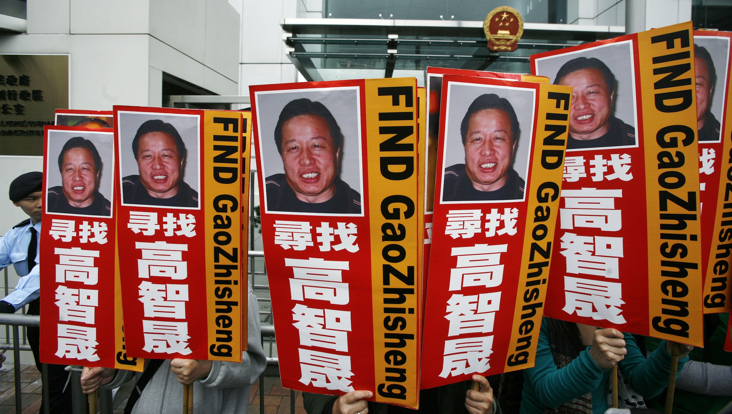 "A policeman stands guard as protesters carrying portraits of one of China's most prominent dissidents, Gao Zhisheng, demonstrate outside a Chinese liaison office in Hong Kong February 4, 2010. Gao, an outspoken lawyer who took on sensitive cases that riled China's ruling Communist Party, has been missing for one year. Chinese characters read ""Look for Gao Zhisheng"".   REUTERS/Bobby Yip  (CHINA - Tags: CIVIL UNREST POLITICS) - RTR29T9Z"
