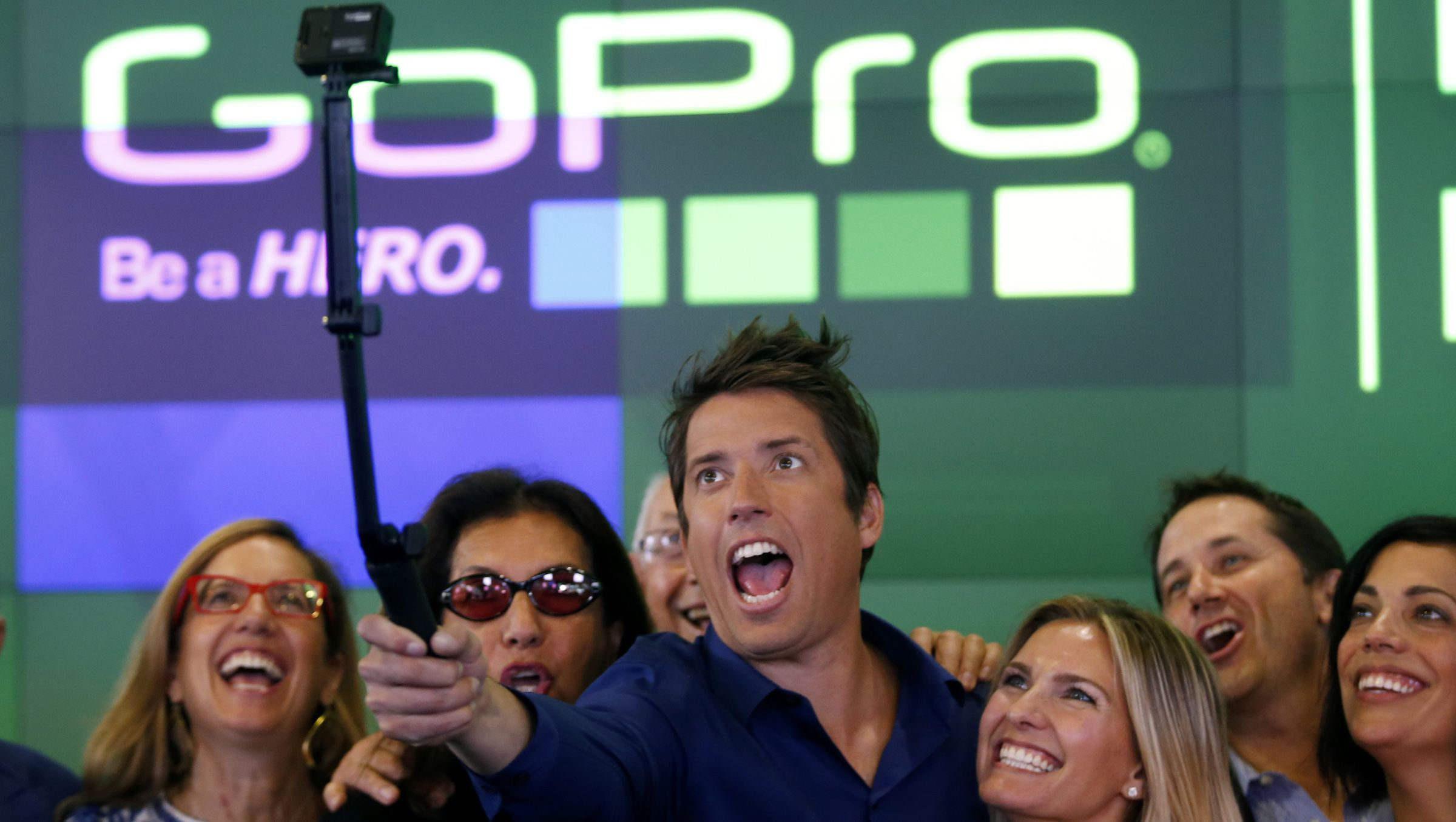 GoPro Inc's founder and CEO Nick Woodman (C) celebrates GoPro Inc's IPO with family and staff at the Nasdaq Market Site in New York City, June 26, 2014. Wearable sports camera maker GoPro Inc's initial public offering was priced at $24 per share, an underwriter said, valuing the company at up to $2.96 billion. At Woodman's right is his wife Jill.  REUTERS/Mike Segar  (UNITED STATES - Tags: BUSINESS SCIENCE TECHNOLOGY) - RTR3VVL0