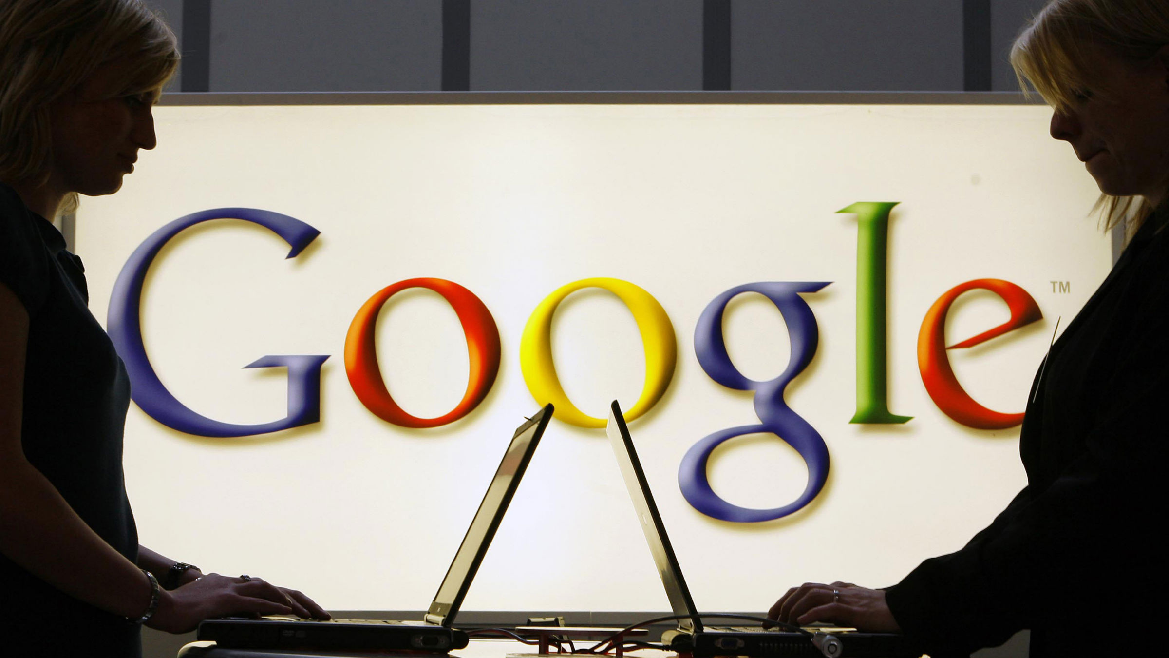 Computer users in front of Google sign