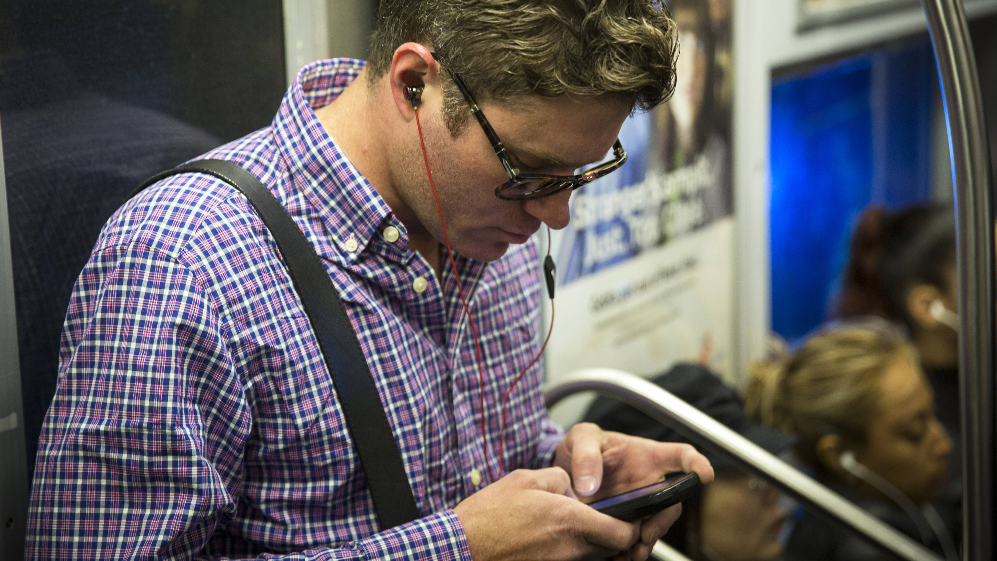 guy reading on smartphone in subway
