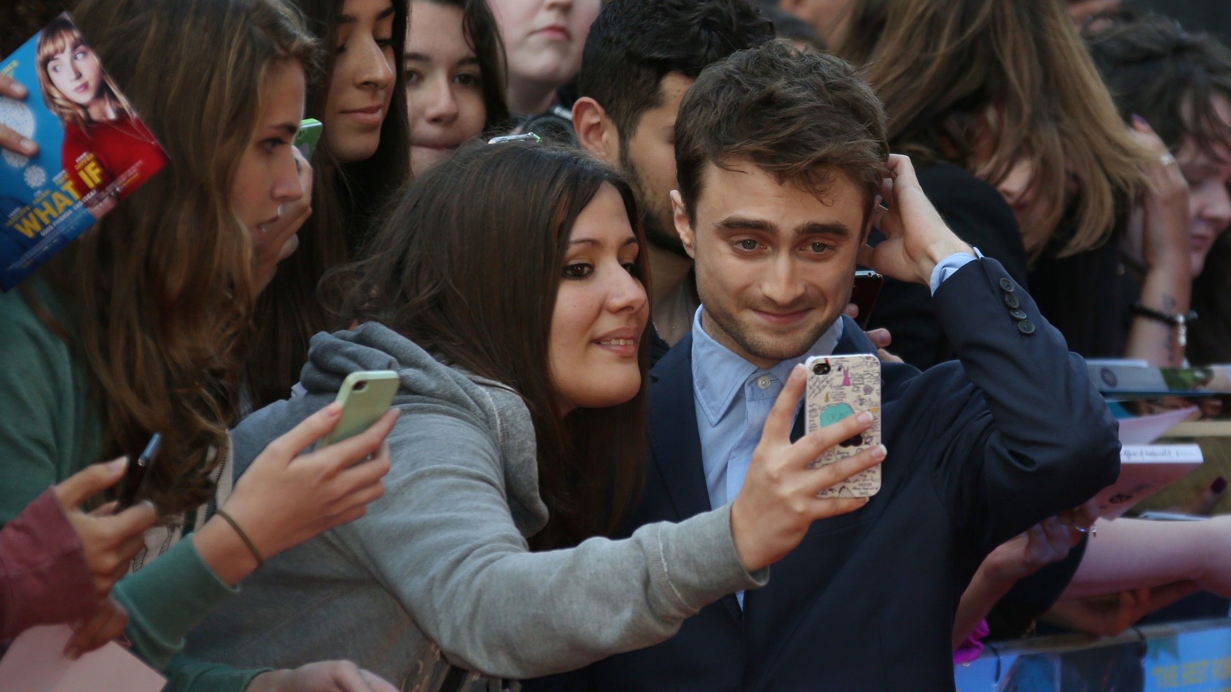 British actor Daniel Radcliffe poses for photographs with fans as he arrives on the red carpet for the UK premiere of What If at the Odeon West End in central London, Tuesday, Aug. 12, 2014. (Photo by Joel Ryan/Invision/AP)
